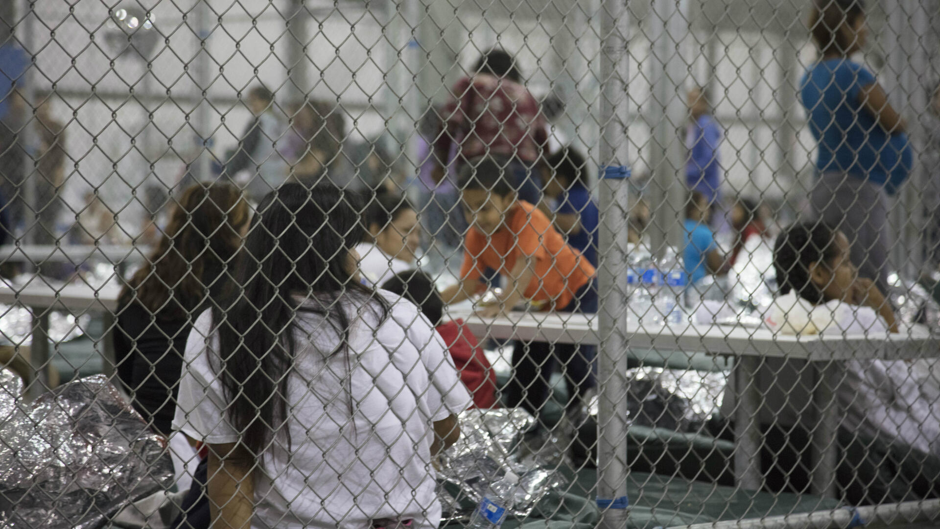 Families detained behind a chain-link fence inside a U.S. Border Patrol facility in Texas