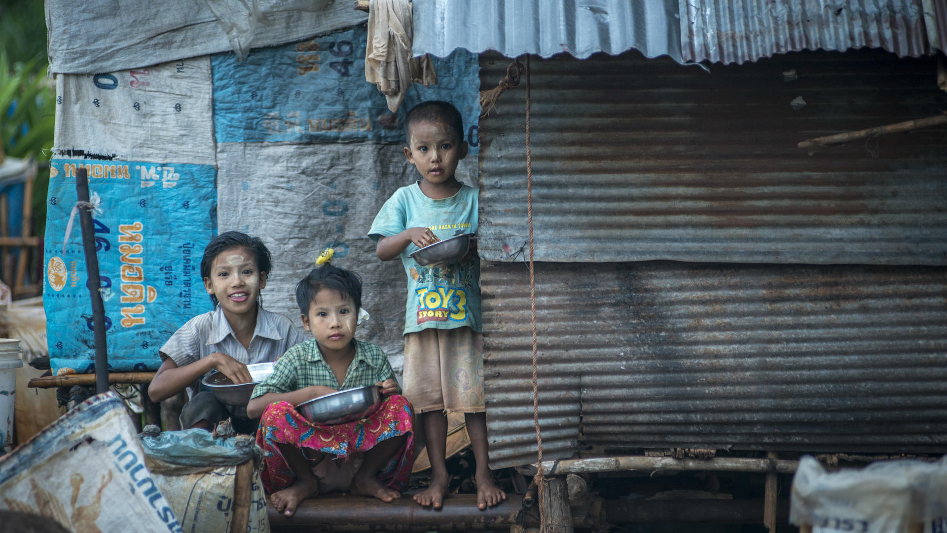 Children sit outside a makeshift shelter in a settlement for Burmese migrant workers near Mae Sot, Thailand.