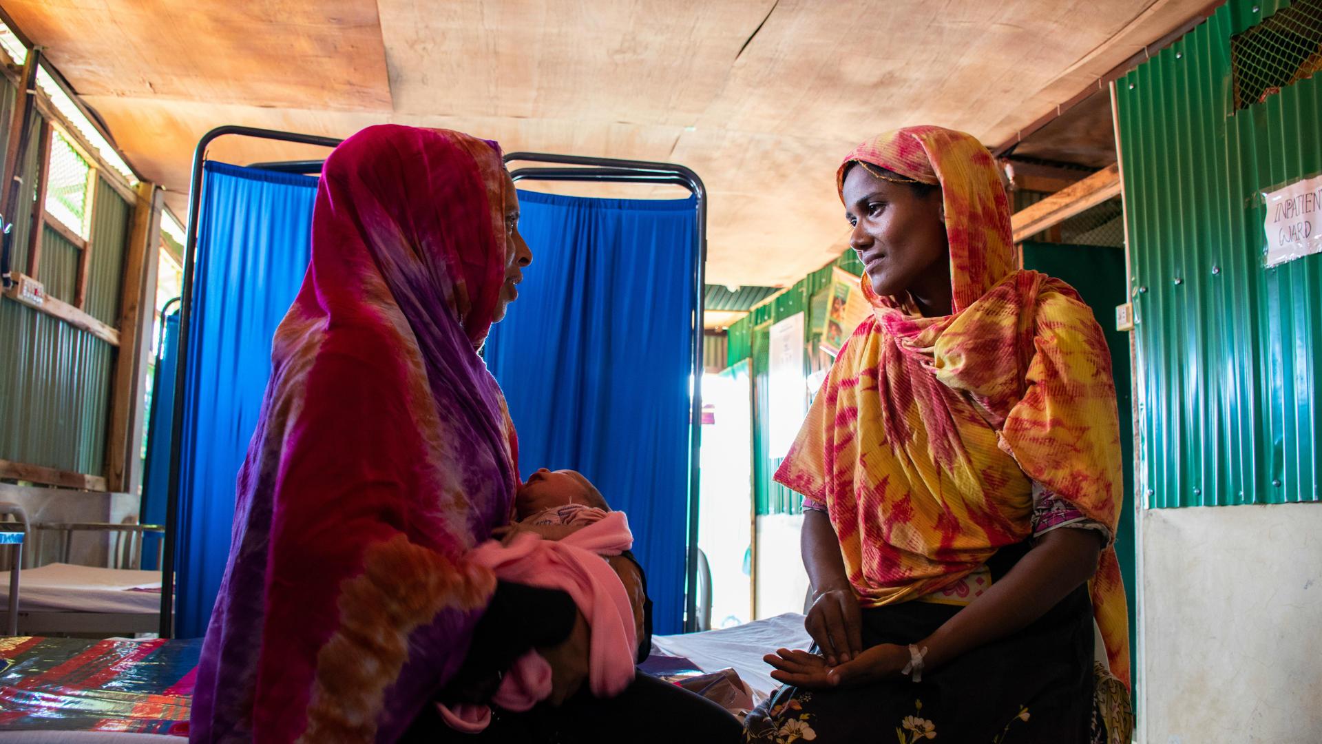 Fatima visits Shahera and her newborn at the women's health center in Kutupalong refugee camp.