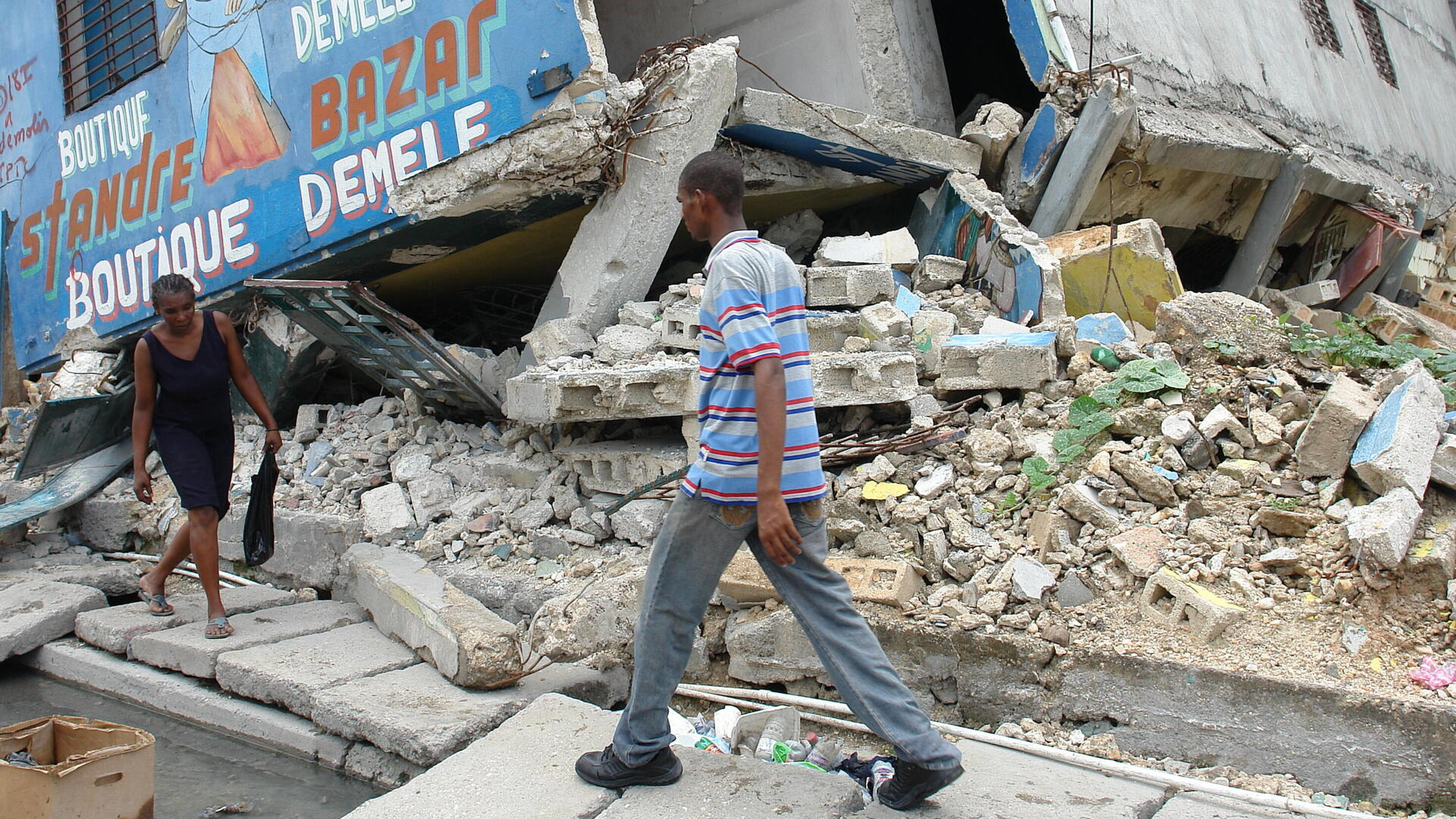A man and woman walk gingerly past the rubble of buildings in Port-au-Prince, Haiti destroyed by the powerful 2010 earthquake.