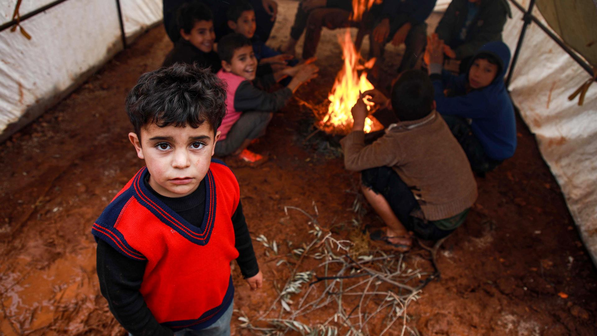 A boy looks on as other children behind sit by a fire inside a tent at a flooded camp for displaced Syrians near the village of Killi in the north of the northwestern Idlib province on December 5, 2019. (Photo by Aaref WATAD / AFP) (Photo by AAREF WATAD/A