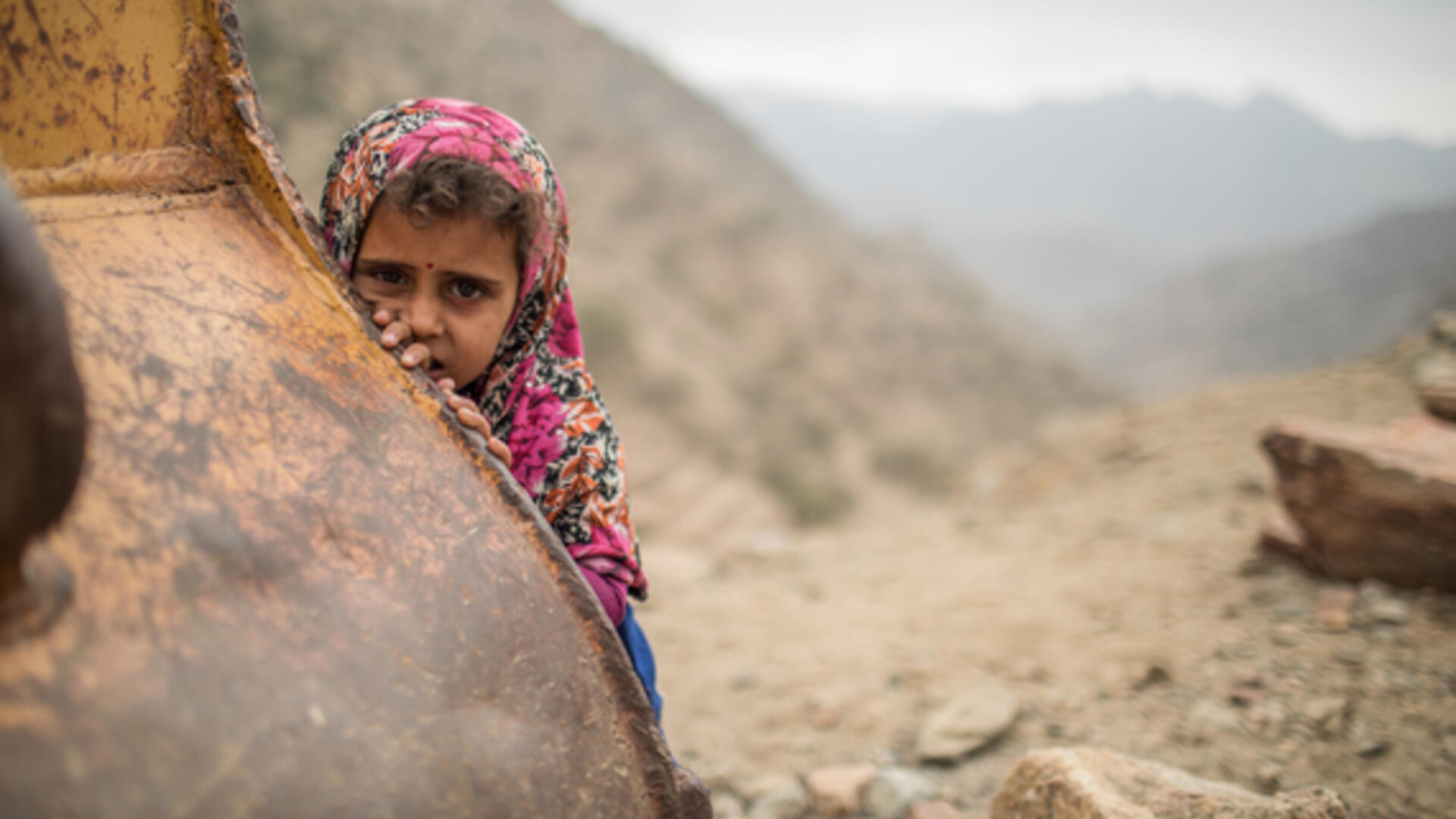 A young girl wearing a pink floral headscarf in a remote mountain area of Yemen