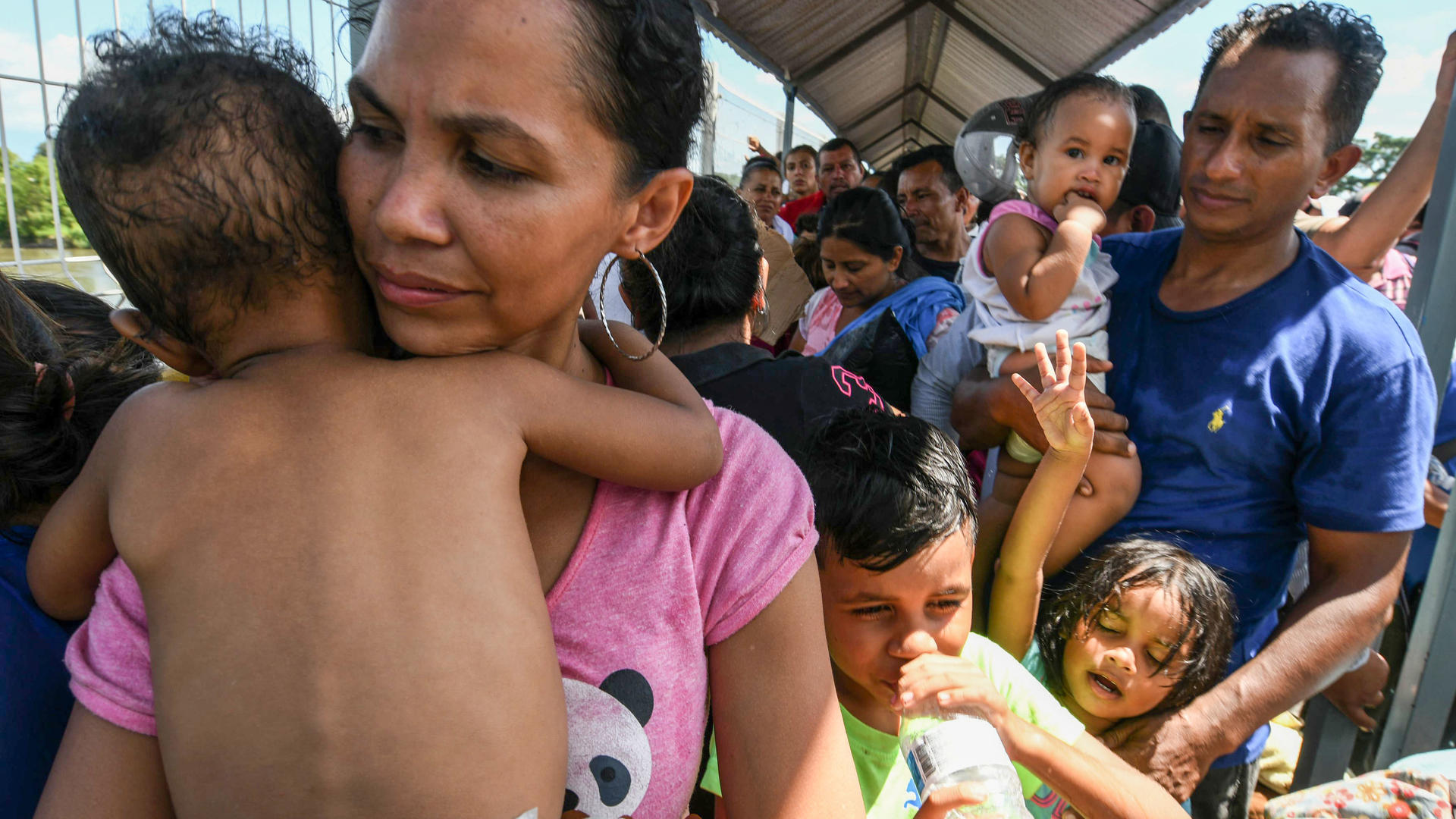 A Honduran migrant couple and their five kids taking part in a caravan heading to the US, wait to cross the border from Ciudad Tecun Uman in Guatemala, to Ciudad Hidalgo, Mexico. Photo: ORLANDO SIERRA/AFP/Getty Images