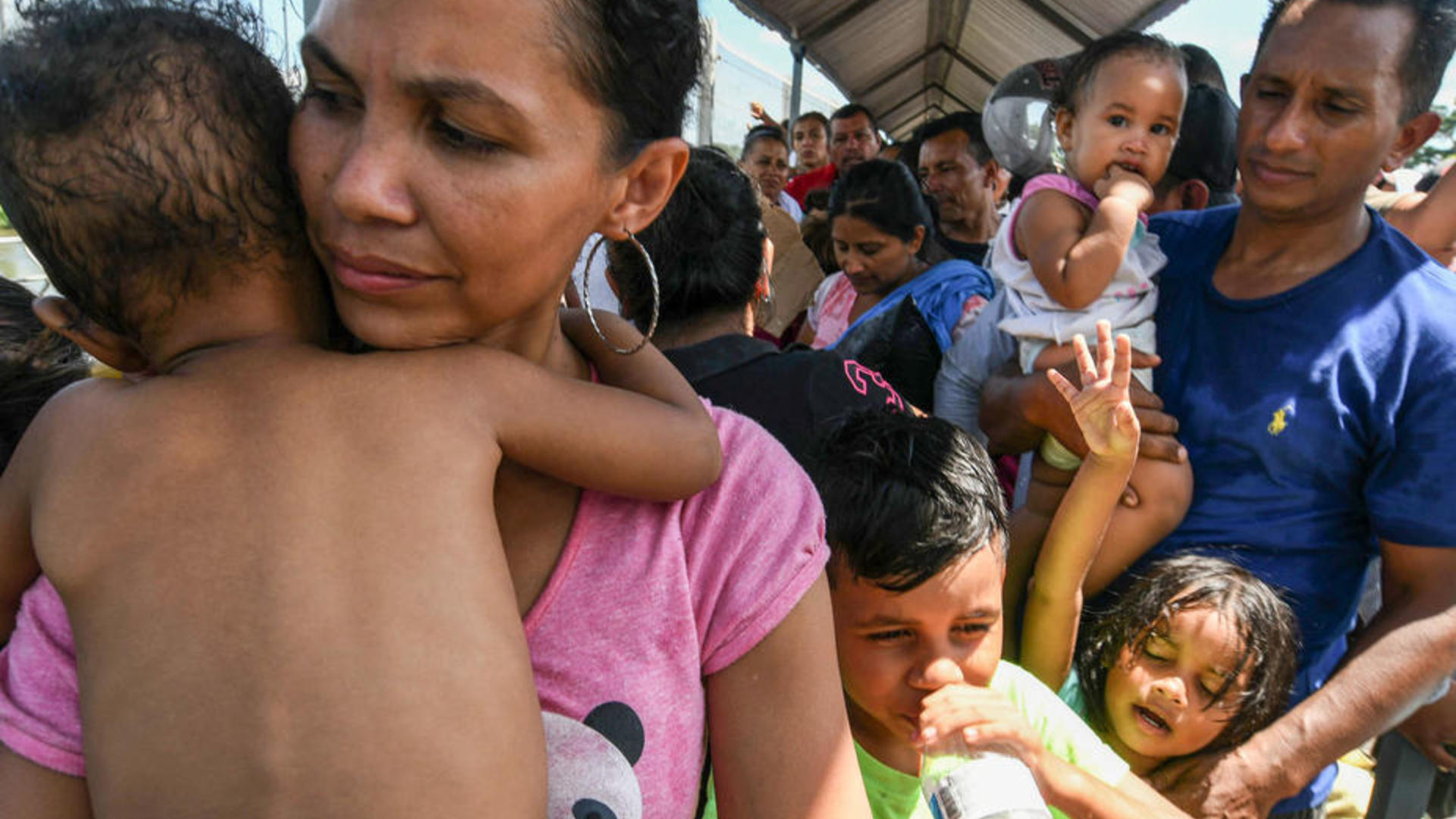 A family fleeing violence in Honduras waits to cross into Mexico on their way to seek asylum in the U.S.