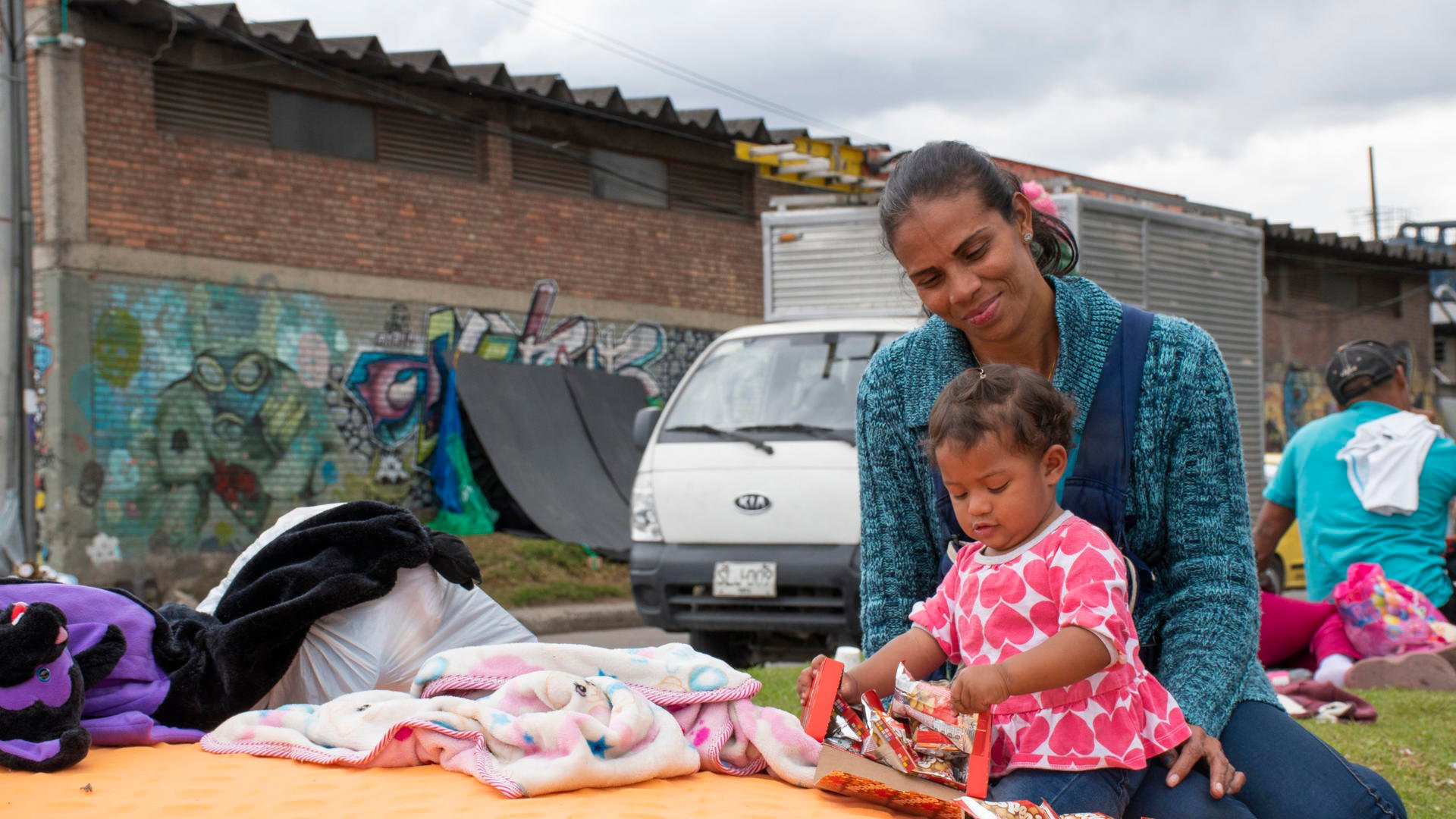 Carina plays with her daughter Kimberly in her lap, camped alongside other Venezuelan refugees