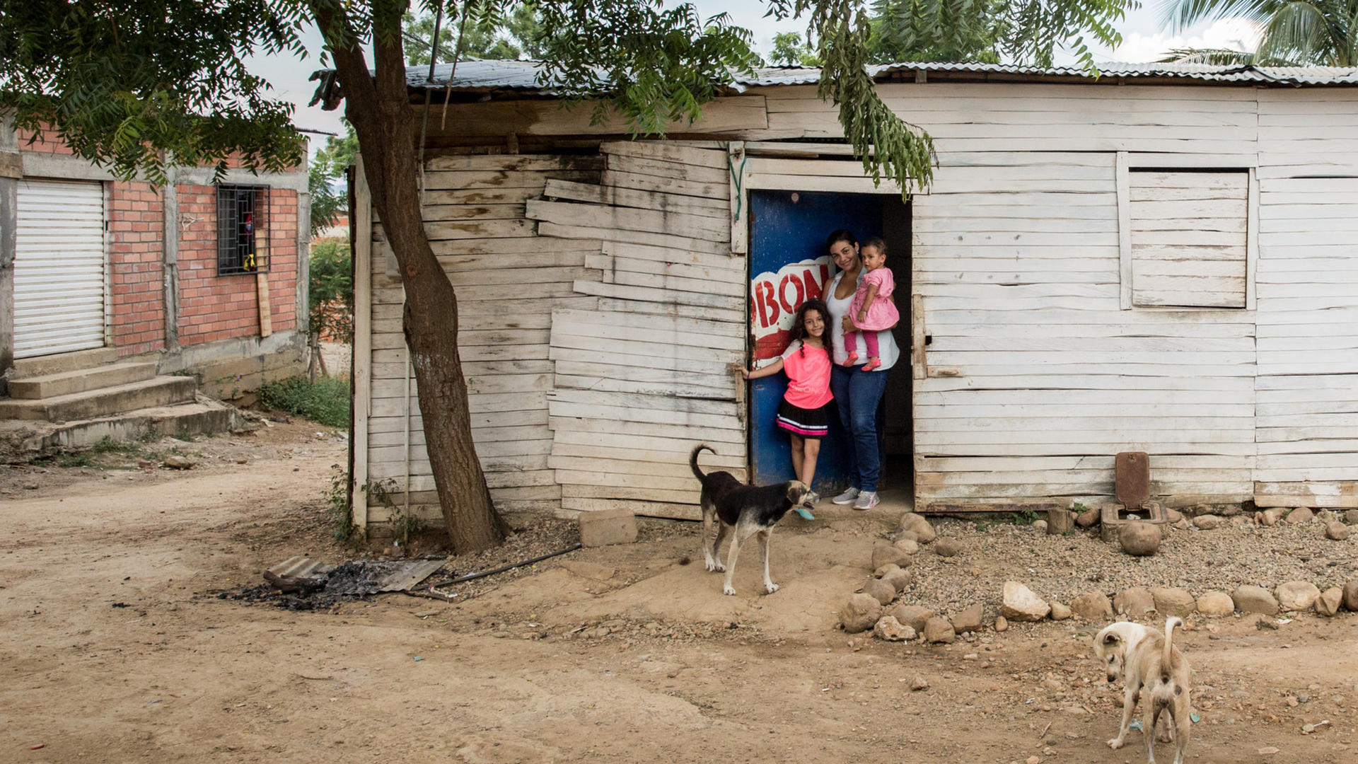 Andrea and her daughters, ages 1 and 9, at the door of the small house their family shares with five other people in Cucuta, Colombia