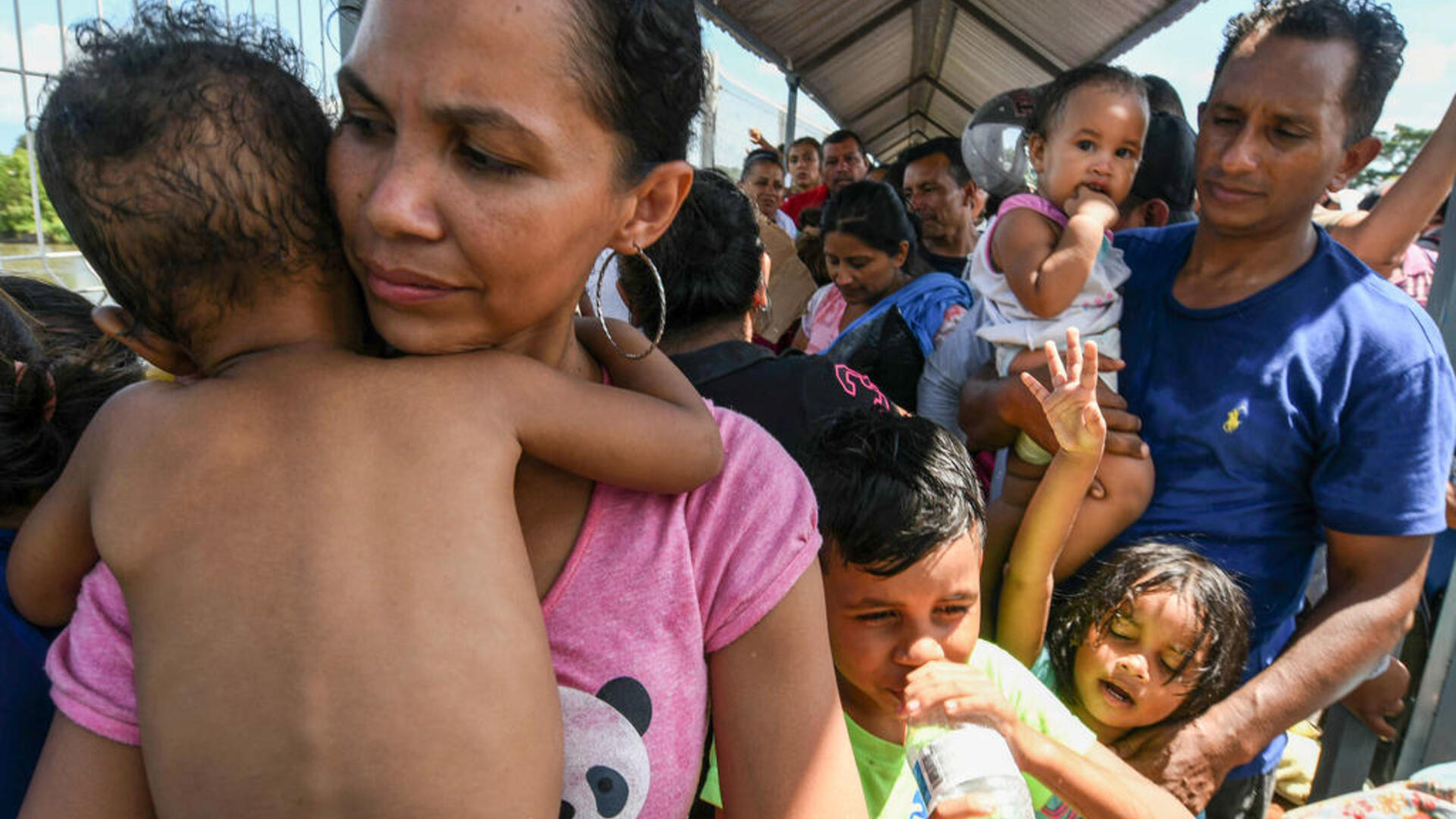 A Honduran couple and their five children, heading to the U.S. in a caravan, wait to cross into Mexico