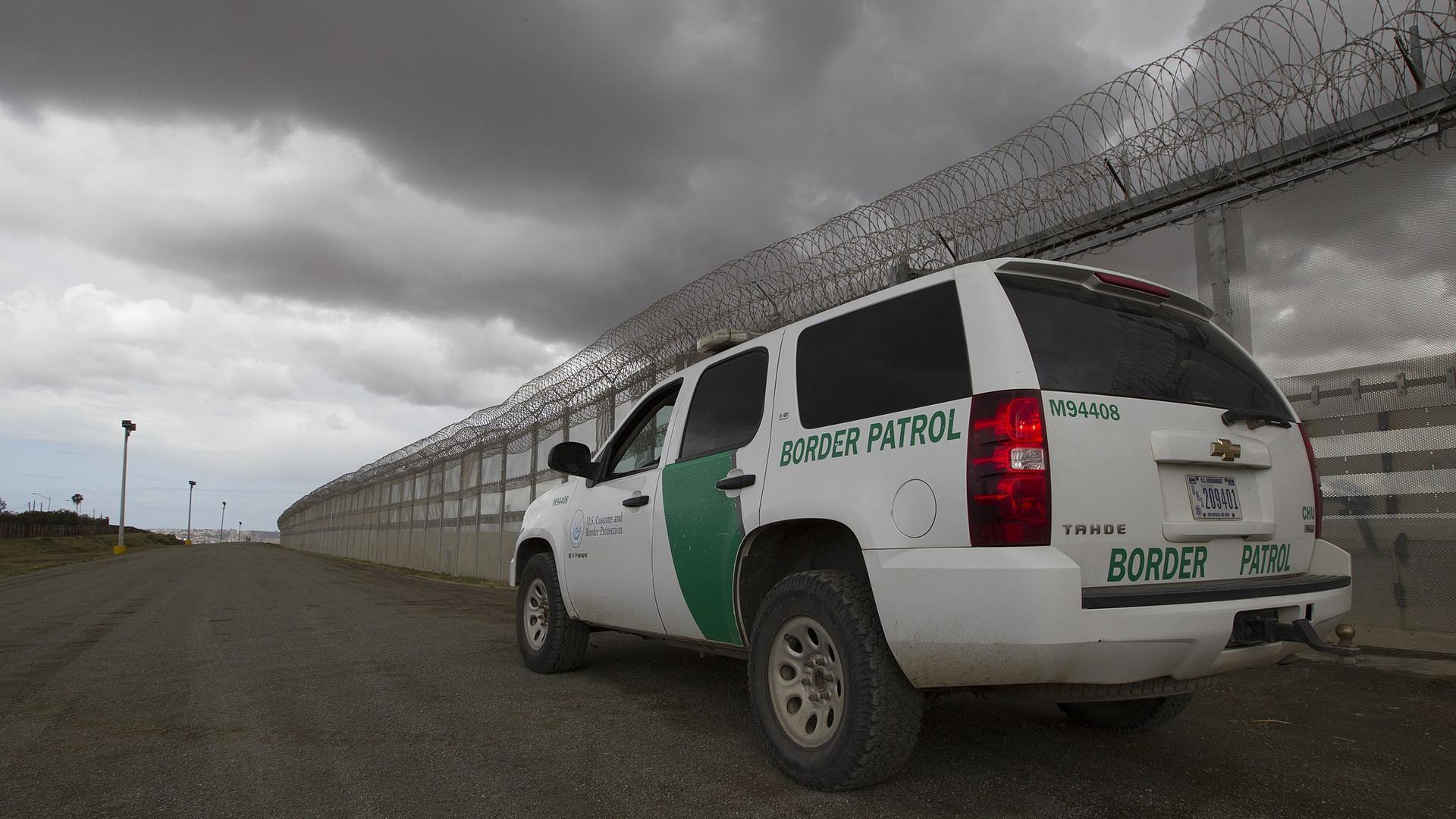 U.S. Border Patrol vehicle at a border fence near San Diego