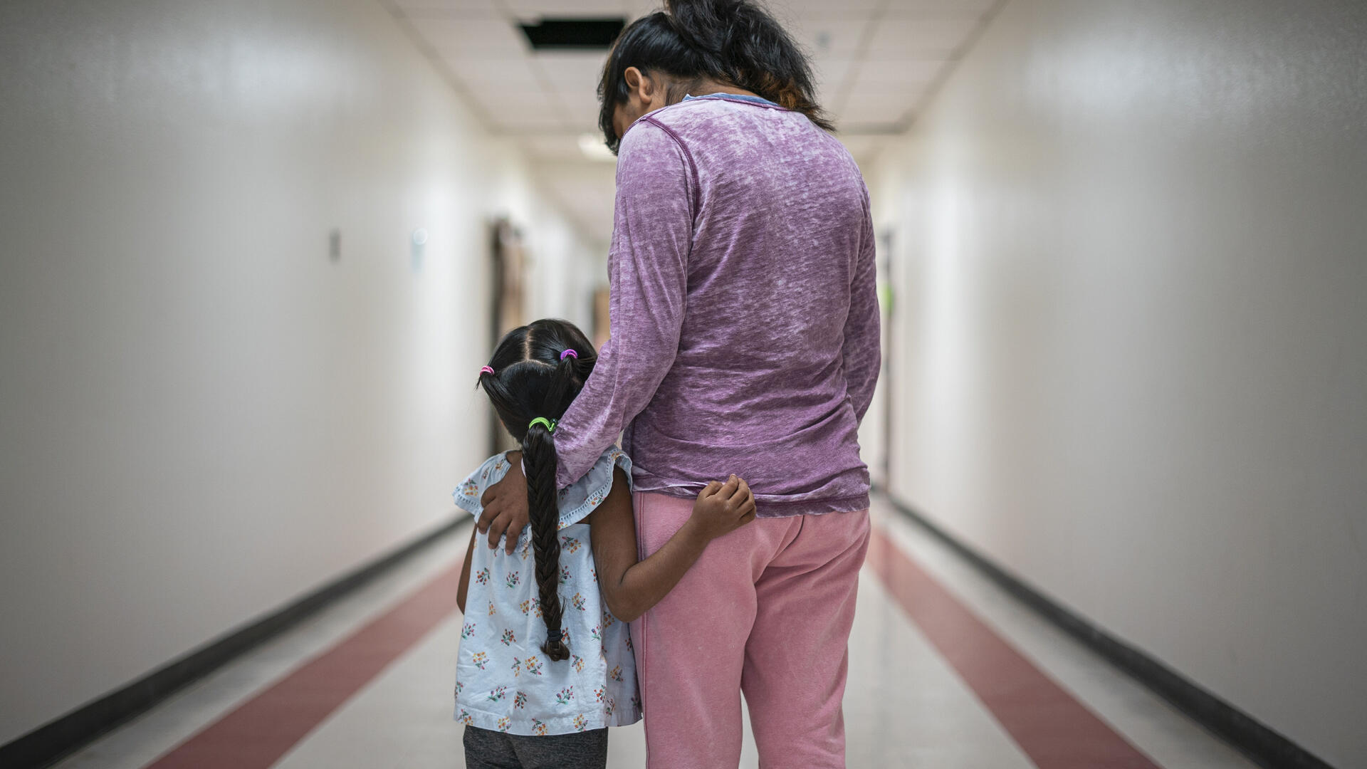 A Mexican mother wearing pink pants and a purple shirt stands with her arms around her young daughter, who has a long braid, in a hallway. They are asylum seekers in an IRC welcome center.