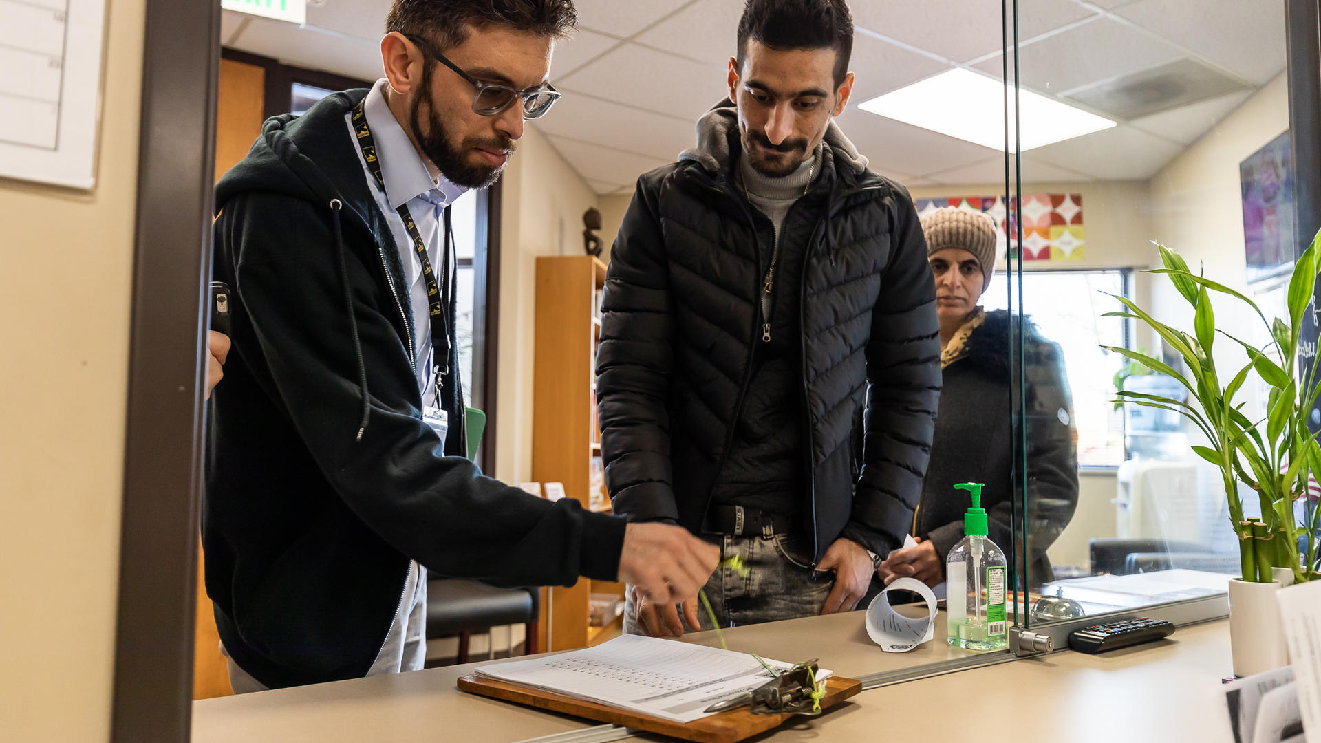 IRC caseworker Qais Nayab and Iranian refugees Sirvan and Saltanat Moradi at IRC offices located in SeaTac, WA