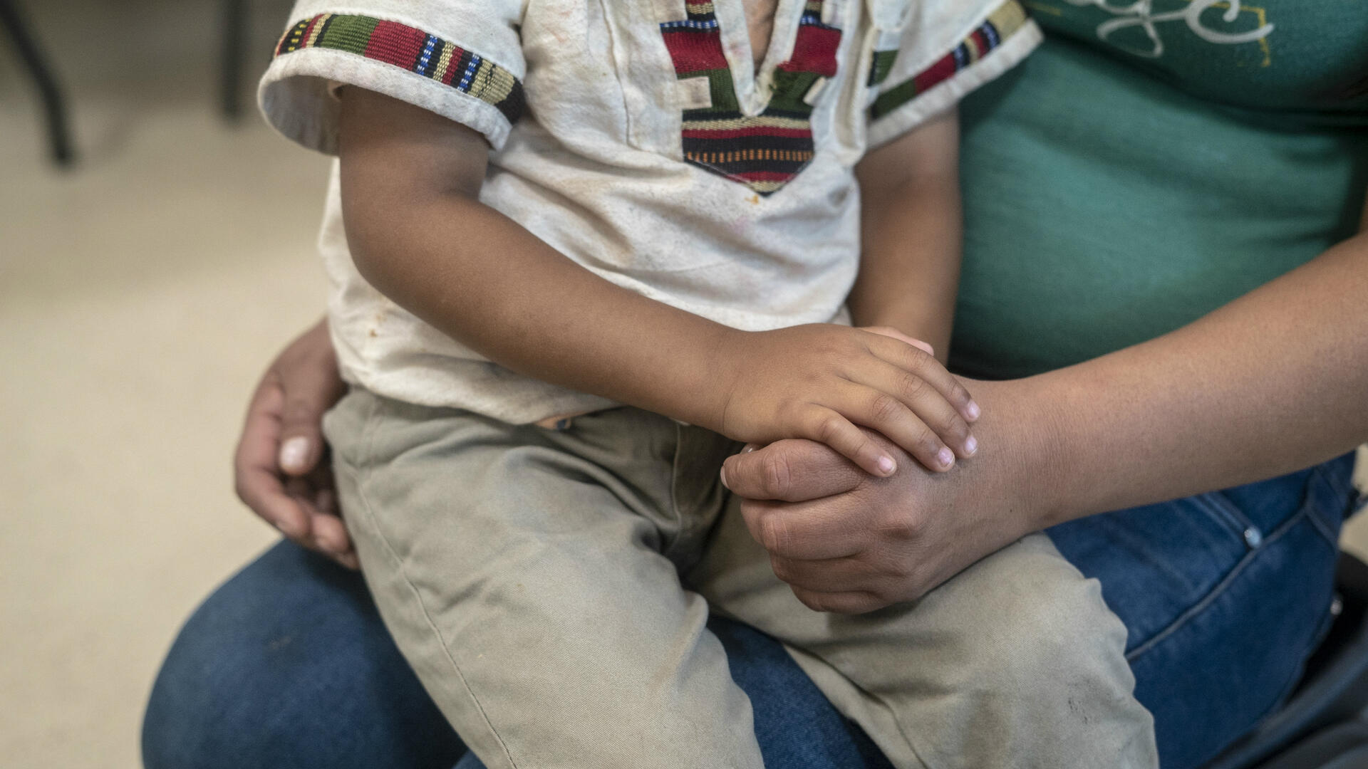 A Central American child sits on his mother's lap at an IRC day center for asylum seekers in Arizona