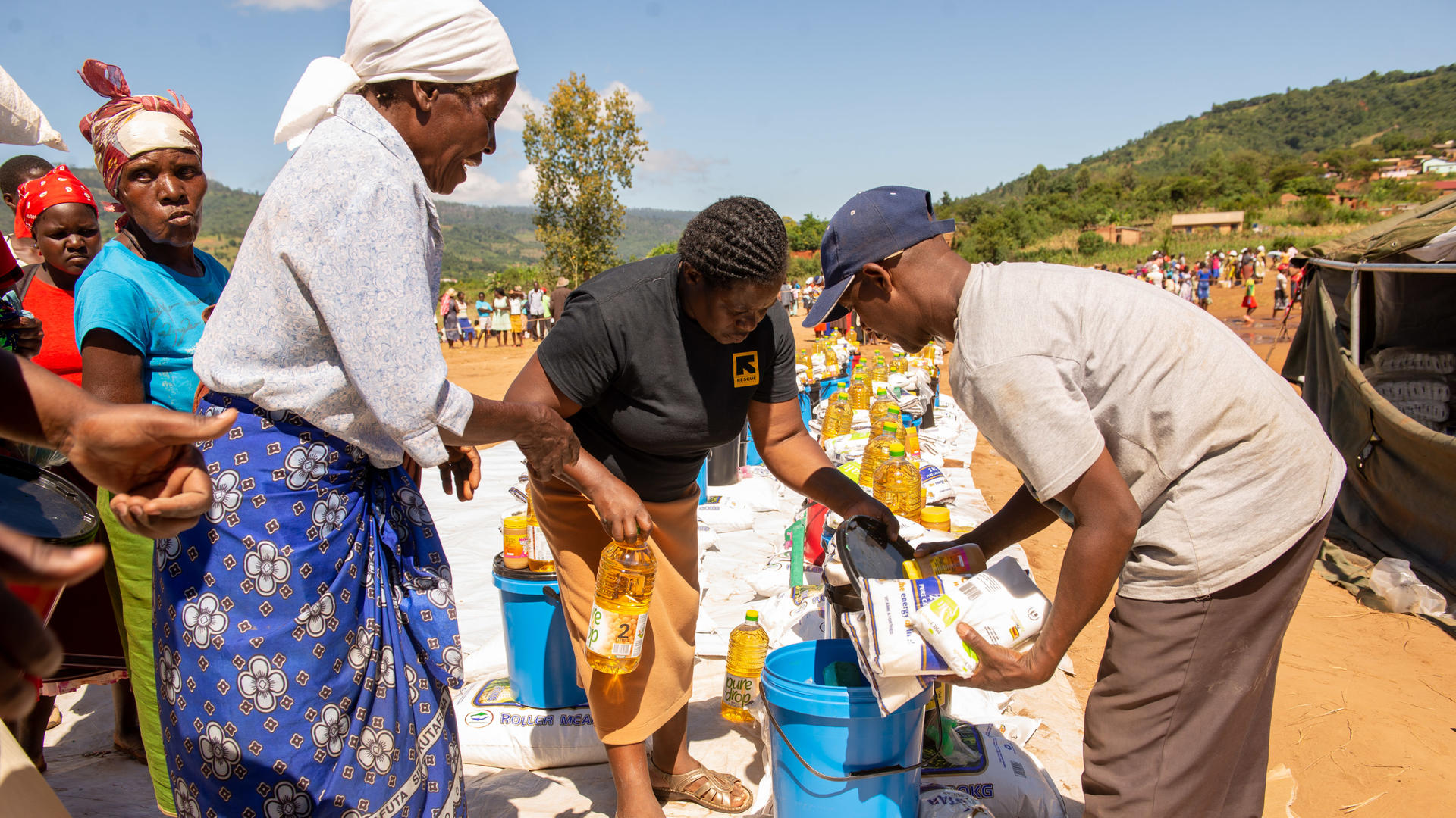 A woman collects food and emergency aid from IRC staff in Zimbabwe after Cyclone Idai
