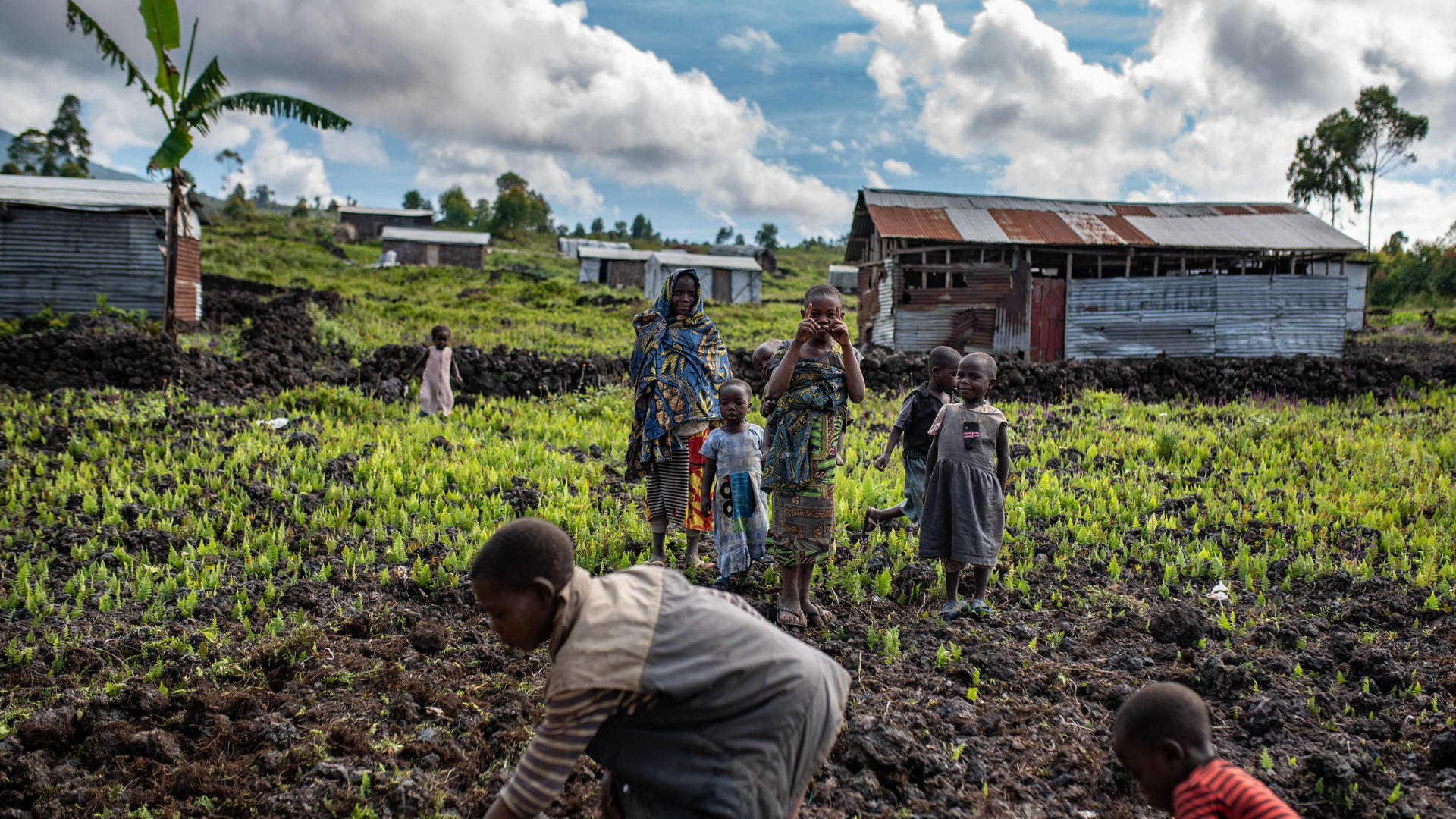 Woman and children work in fields in an area of the Democratic Republic of Congo affected by an Ebola outbreak