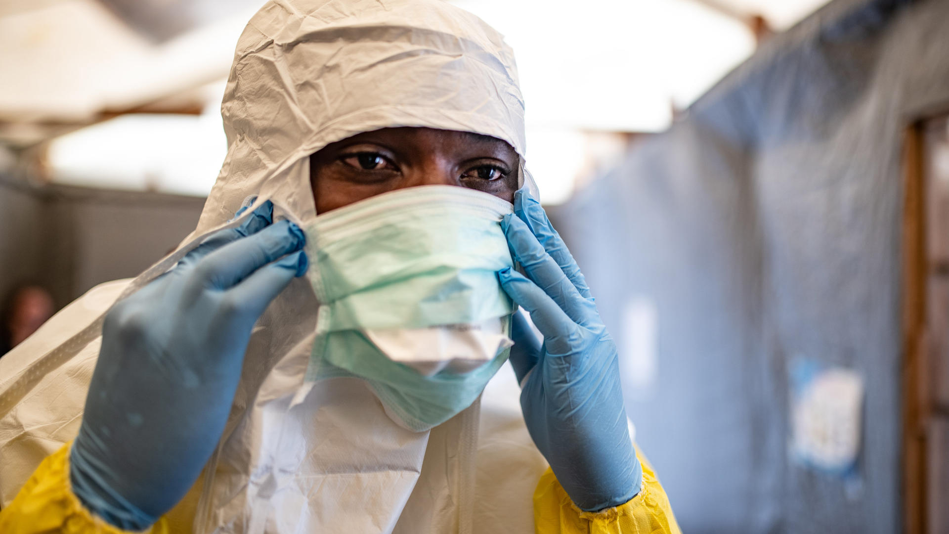A health worker in the Democratic Republic of Congo puts on his protective mask to care for potential Ebola patients