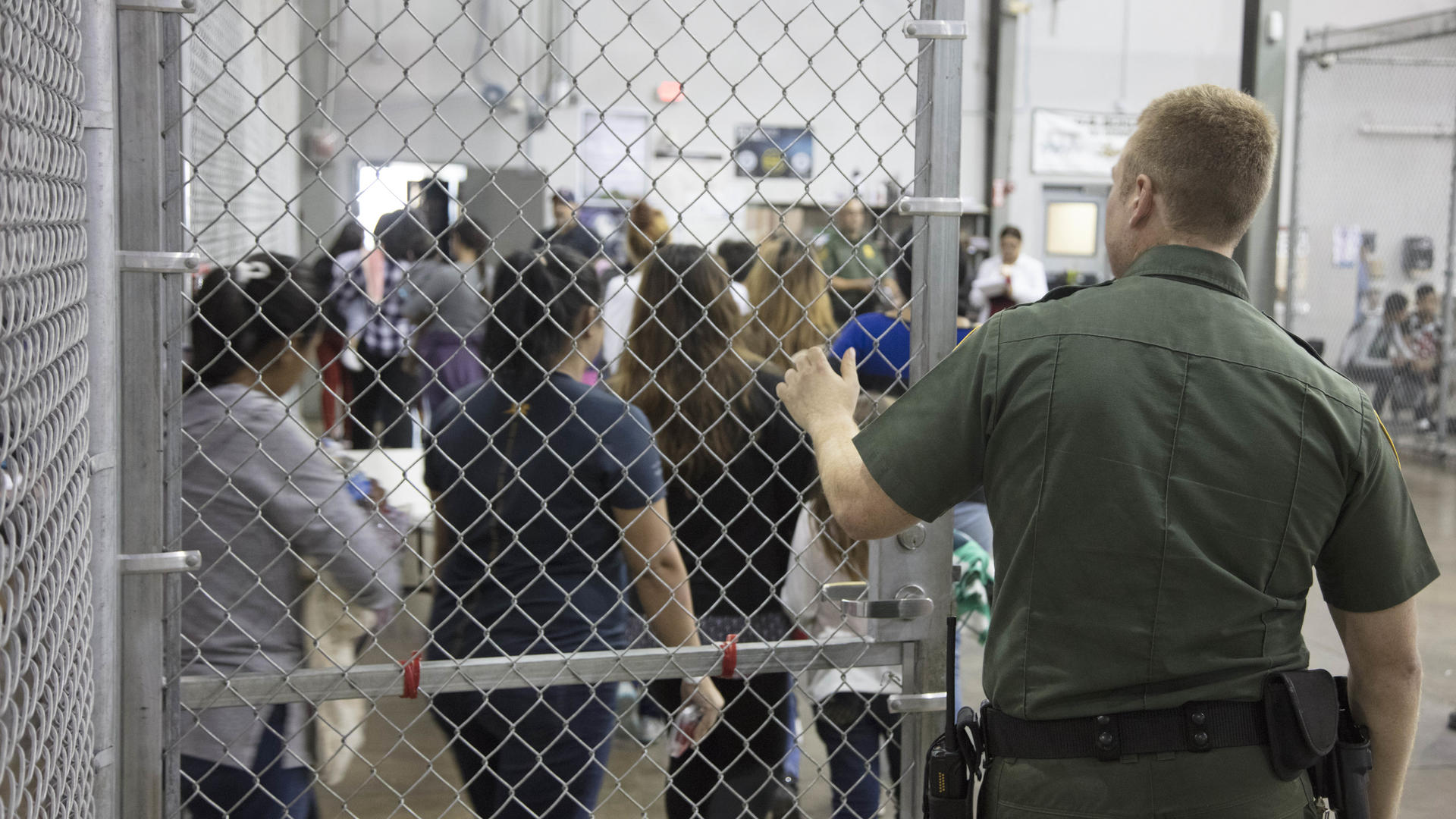 A U.S. border patrol officer at a gate as Central American families enter a detention facility after crossing the U.S.-Mexico border