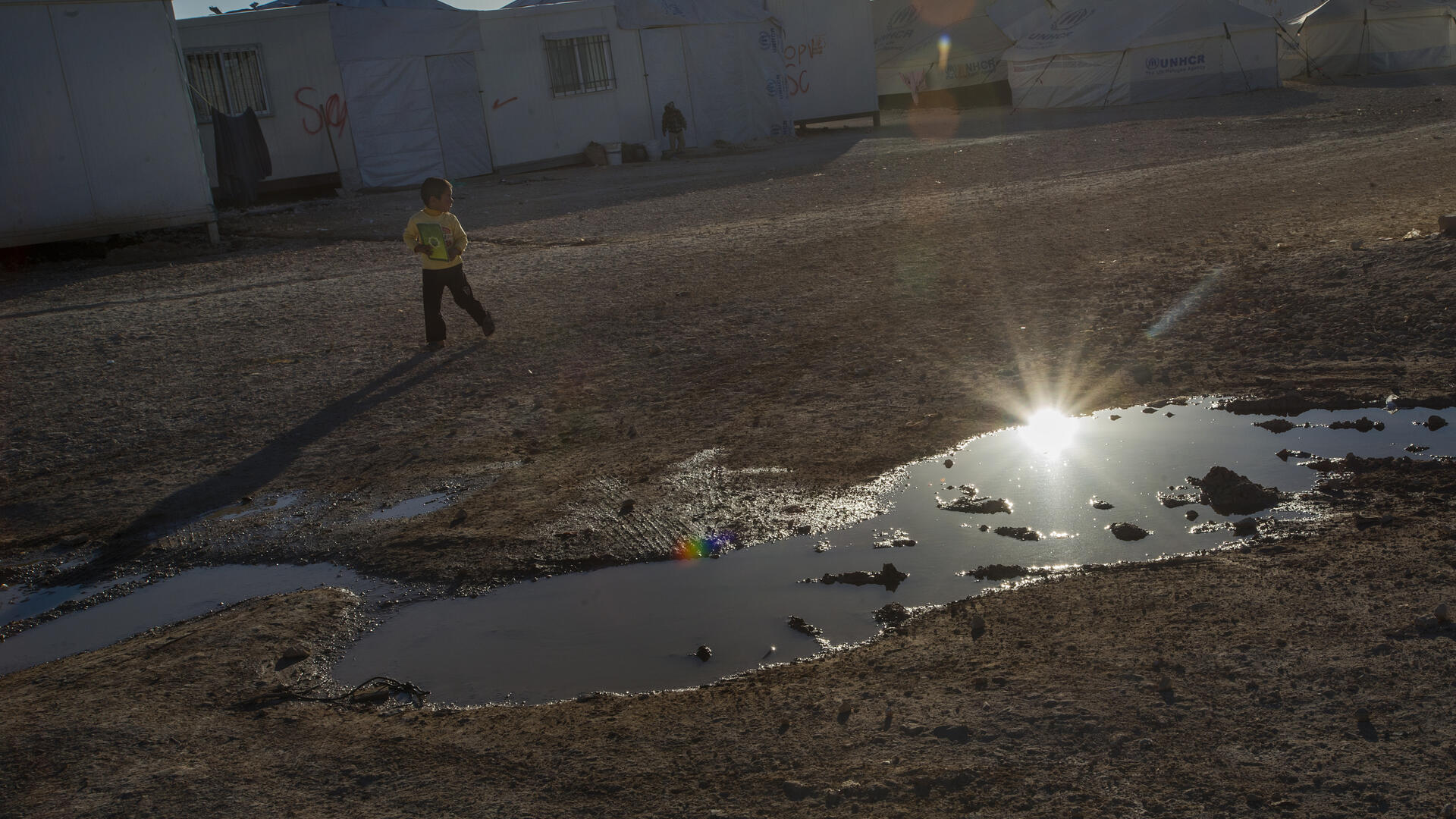 A boy plays near a puddle of waste water at the Zaatari refugee camp in northern Jordan.