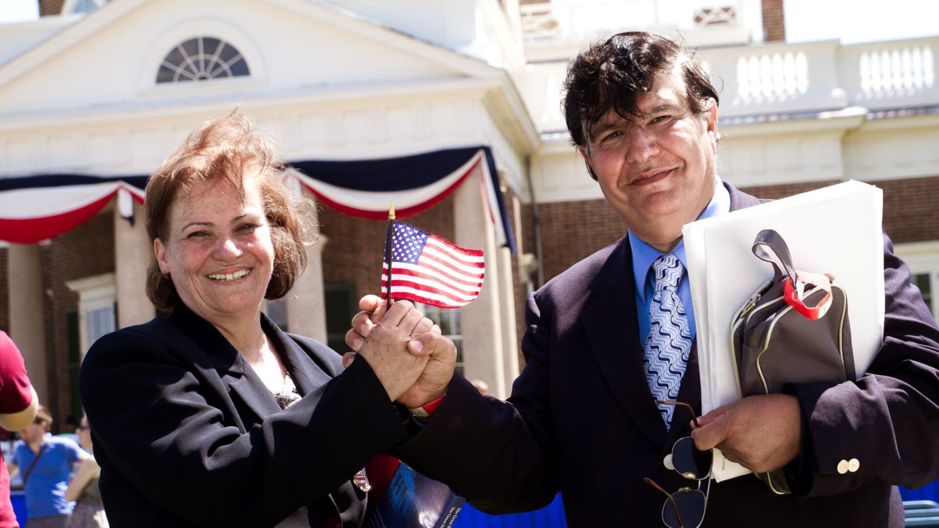 A refugee couple hold a U.S. flag at their naturalization ceremony in Charlottesville, VA