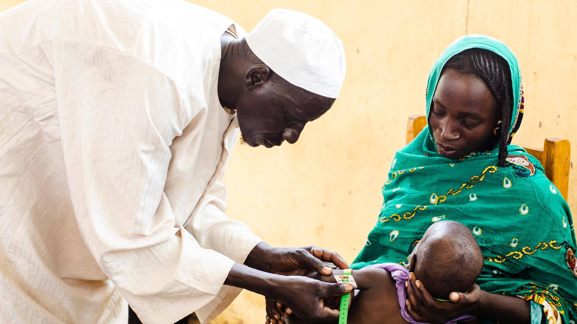 A mother holds her baby during an exam for acute malnutrition at an International Rescue Committee supported health center in Chad.