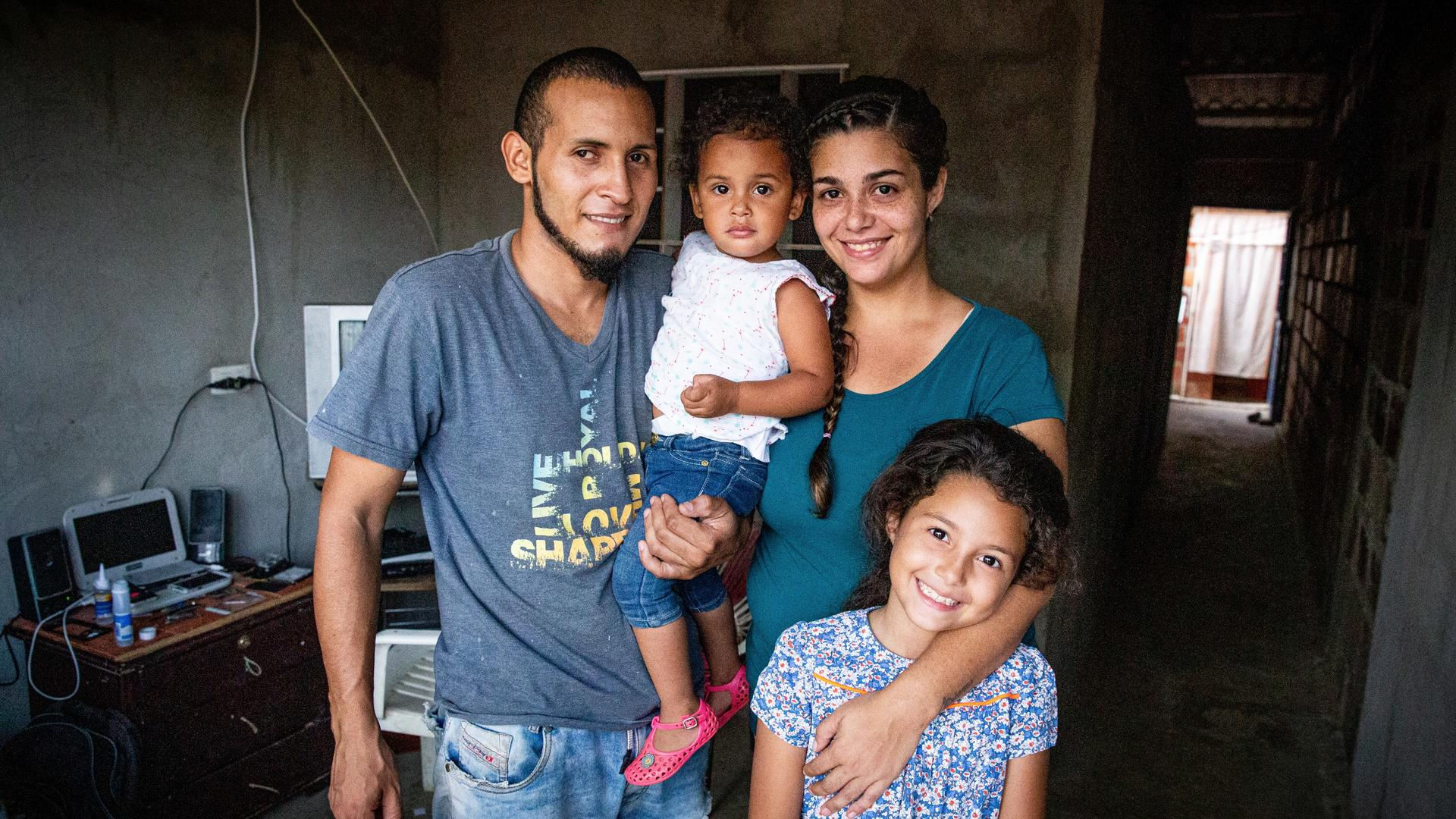 Andrea Rodriguez with her husband and two daughters in their home in Venezuela.