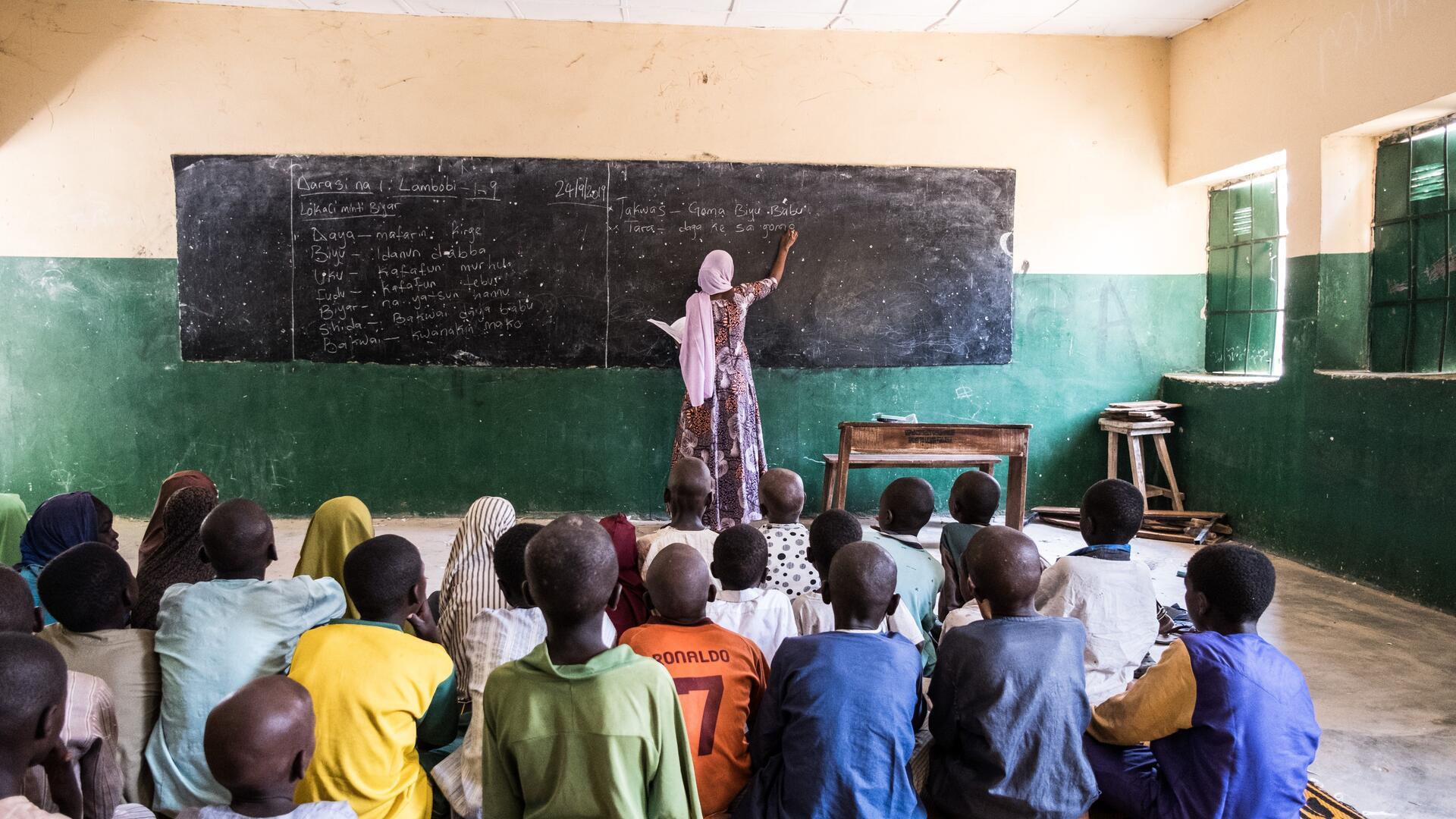 International Rescue Committee teacher Fatima writes on a blackboard in the front of her classroom.