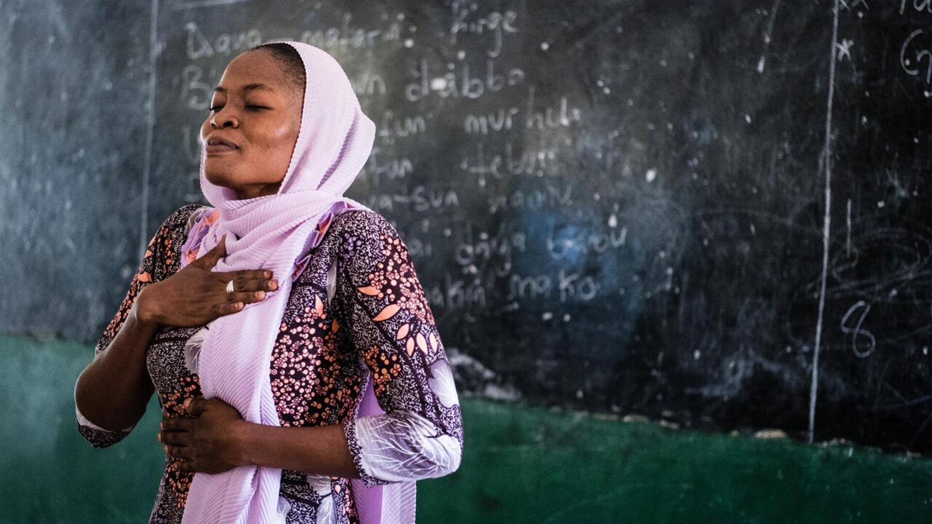 A teacher in Nigeria demonstrates mindfulness breathing techniques to students