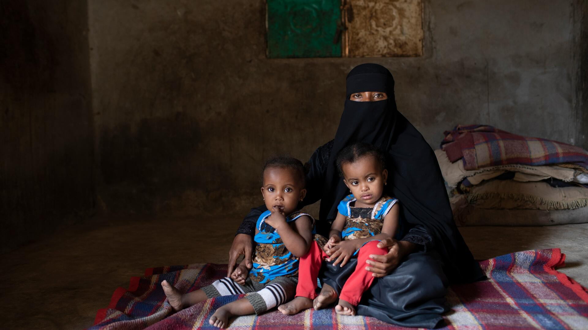 A mother in Yemen sits with her twin daughters