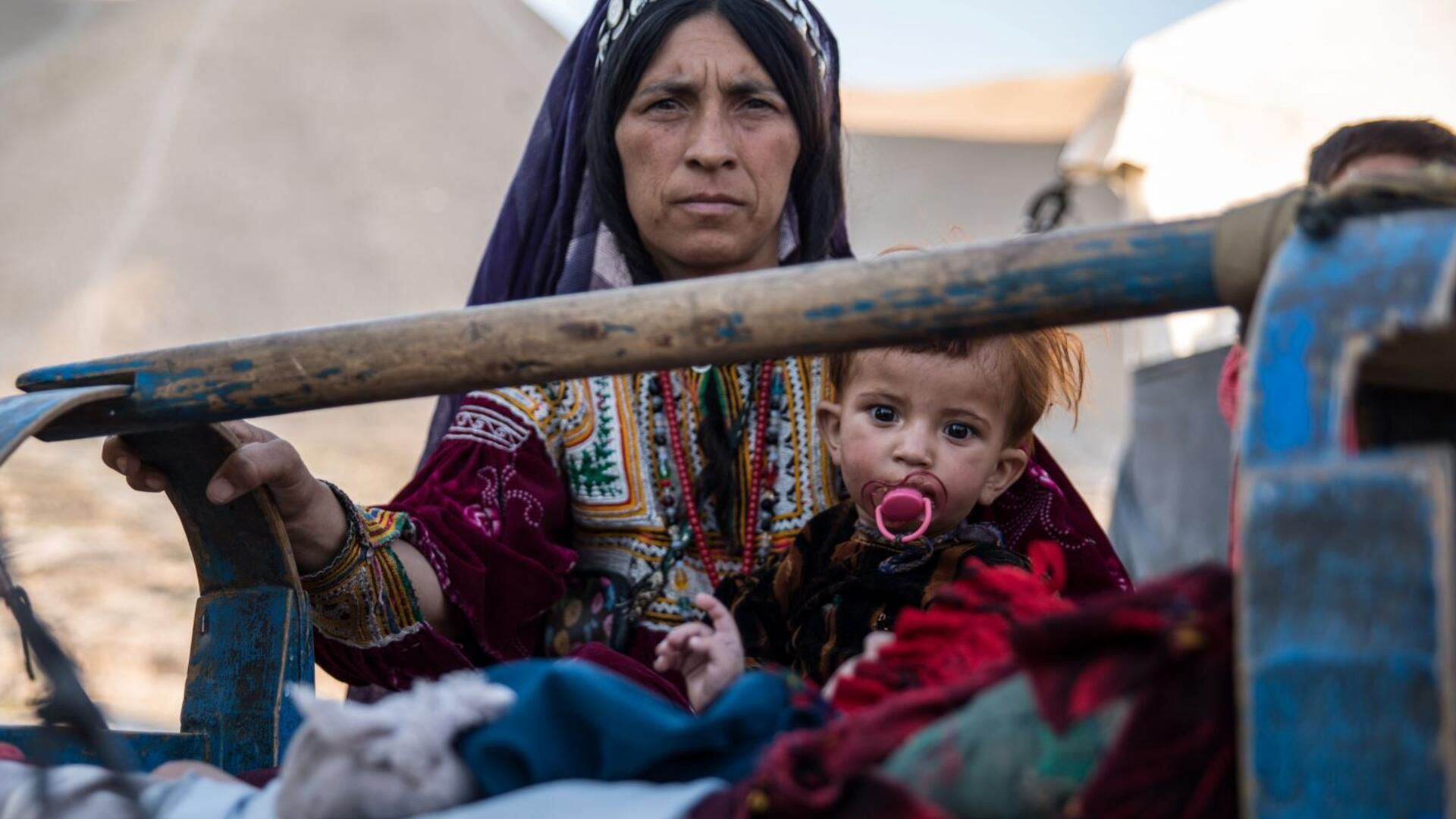 A mother rocks her sick child, who has a pacifier,  in a camp in Badghis