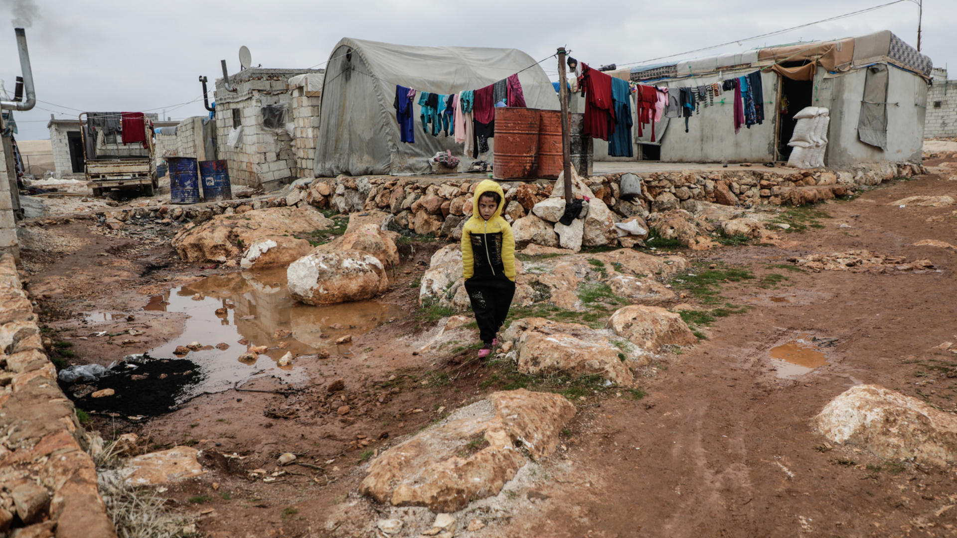 A Syrian boy walks across muddy ground amid tents in Idlib