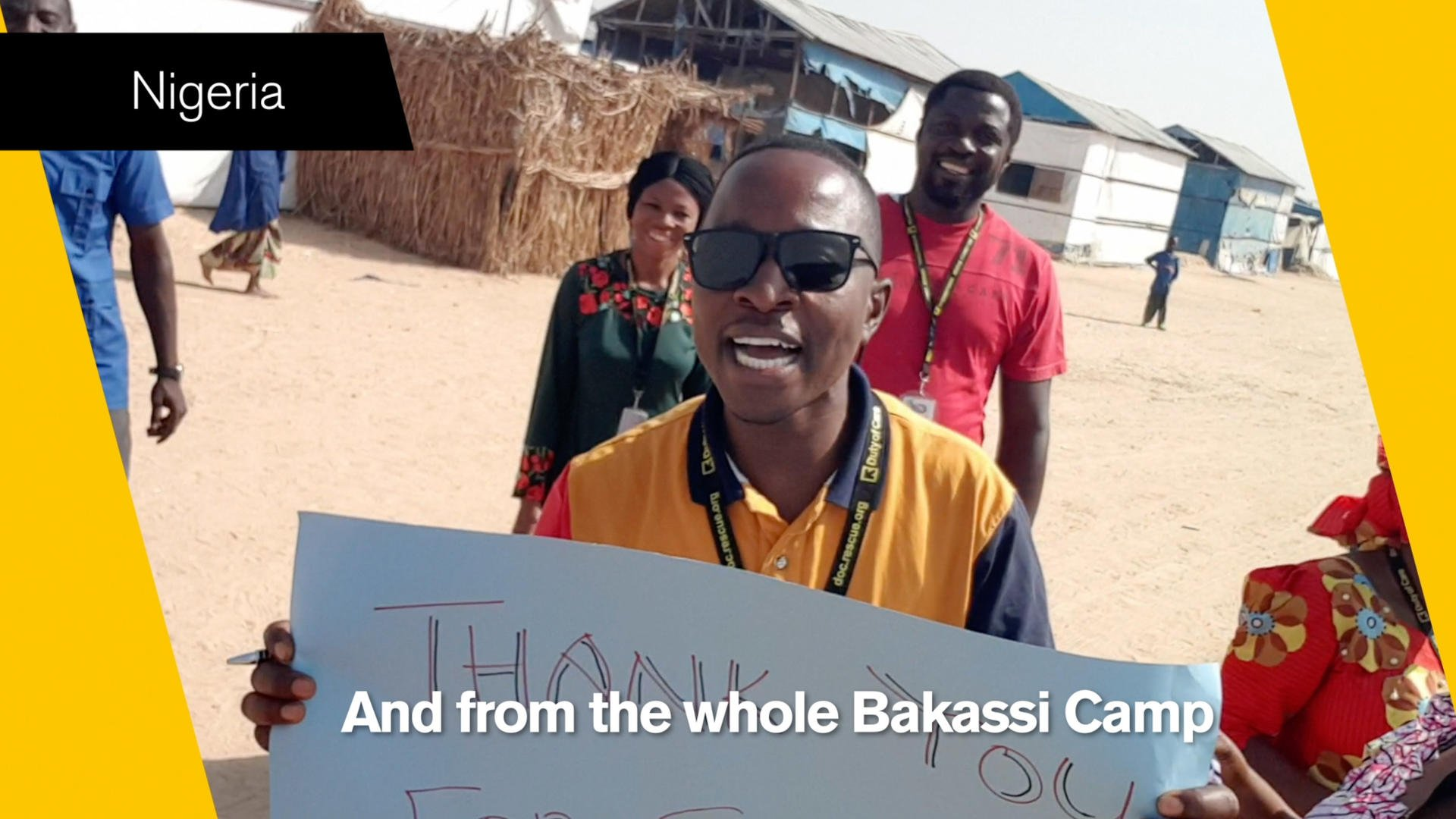 An IRC aid worker in Nigeria holds up a 'thank you' sign in a still from video thanking IRC donors