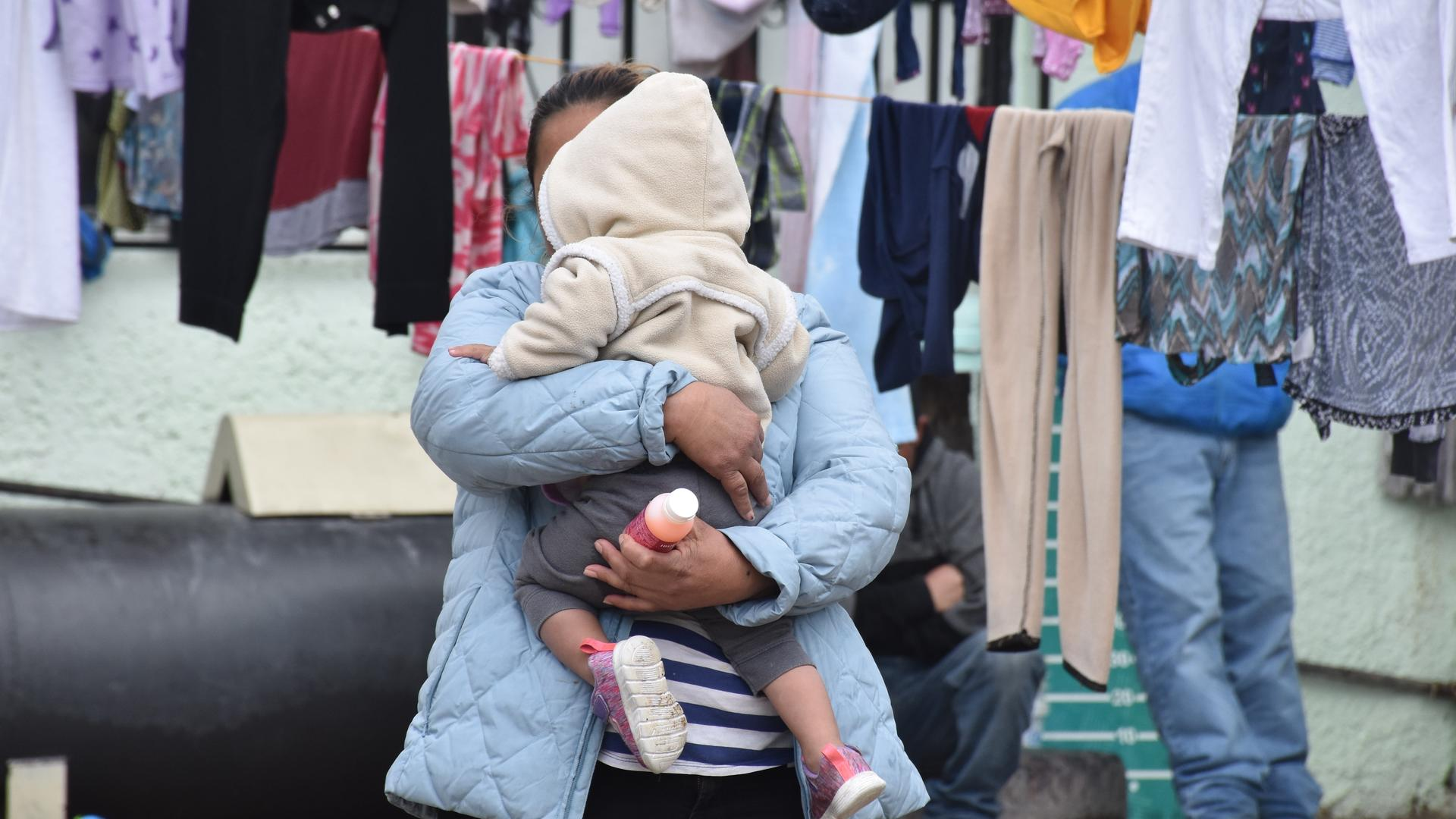 Alma, an asylum seeker from Guatemala, and her daughter wait for their laundry to dry in the outdoor living space of a shelter in Ciudad Juarez.