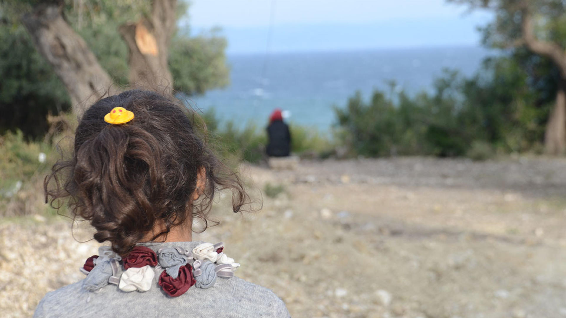 A refugee child on the island of Lebos, in Greece, looks out toward the sea