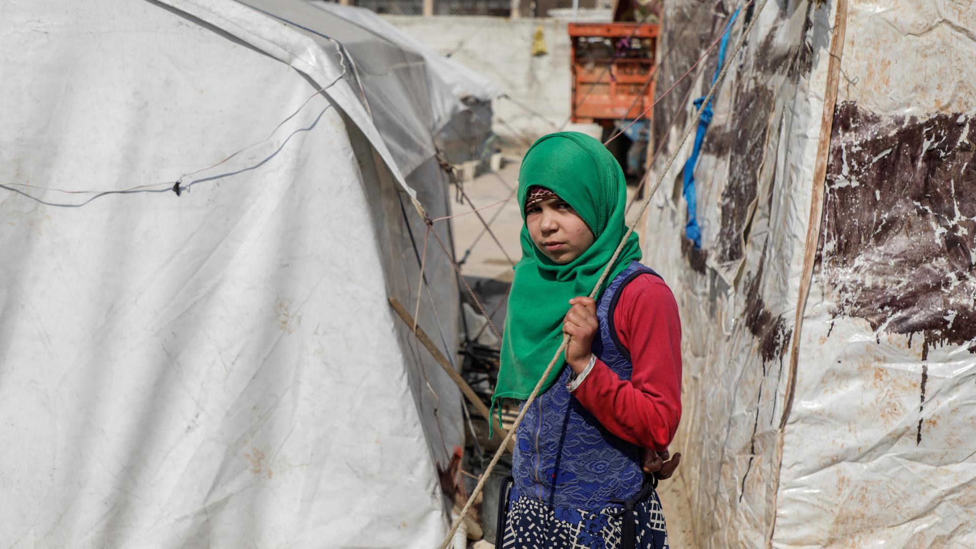 Syrian girl stands in front of her uncle's tent in Idlib countryside
