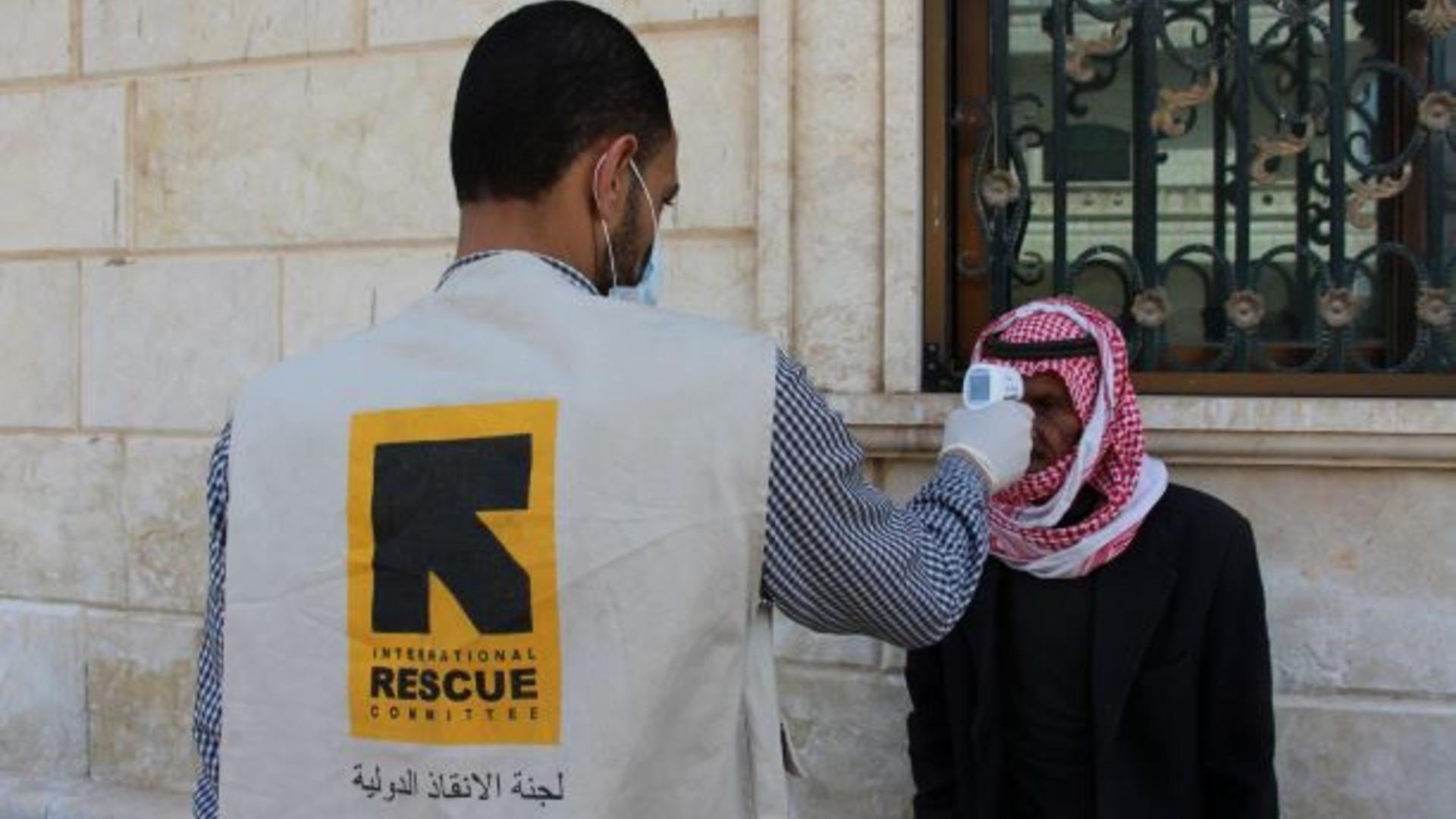 An IRC health worker scans a man in Syria for fever