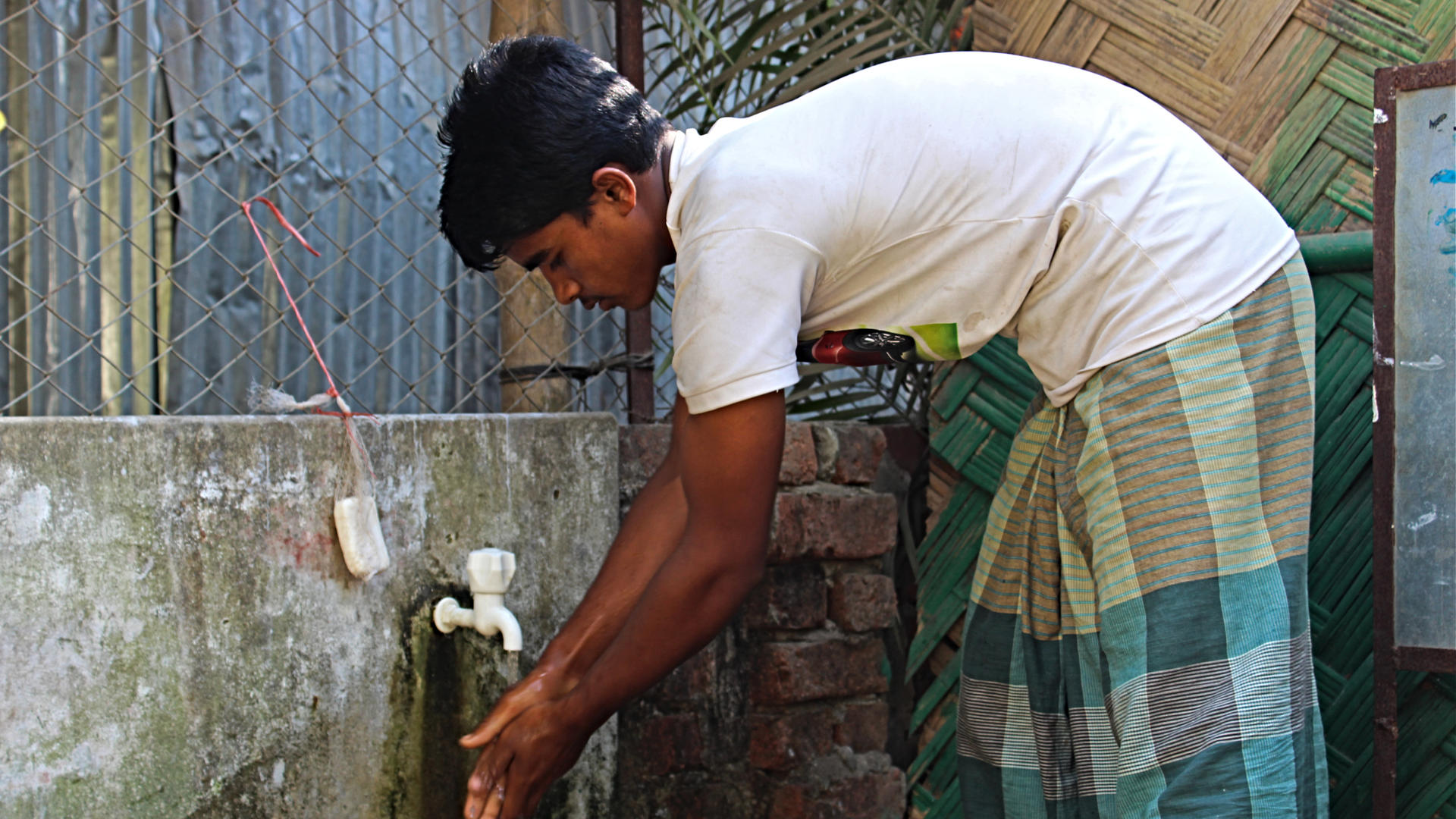 A young refugee washes his hands at a tap in refugee camp where the International Rescue Committee works in Bangladesh.