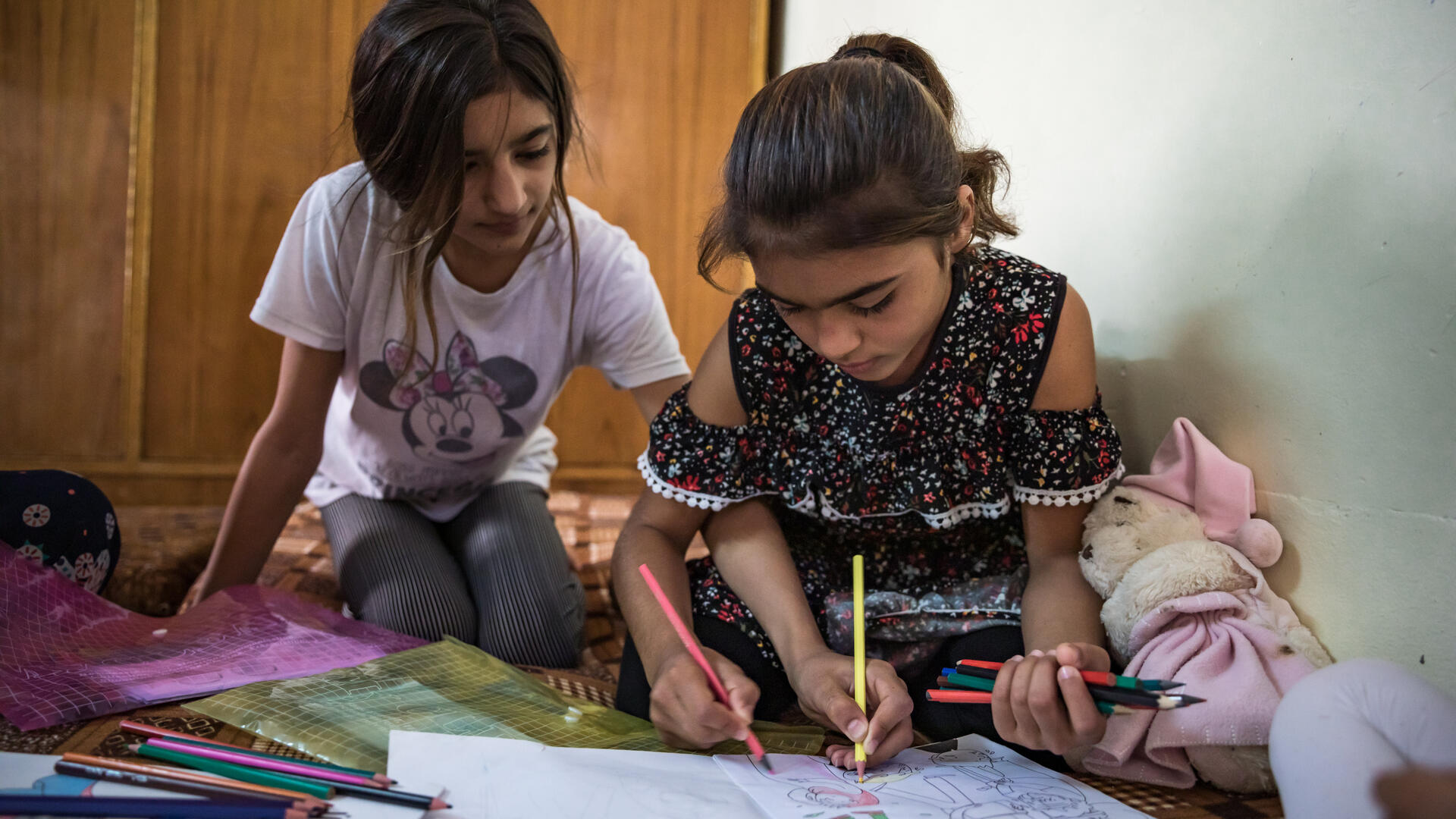 Two Yazidi sisters in Sinjar, Iraq sit on the floor of their home, coloring