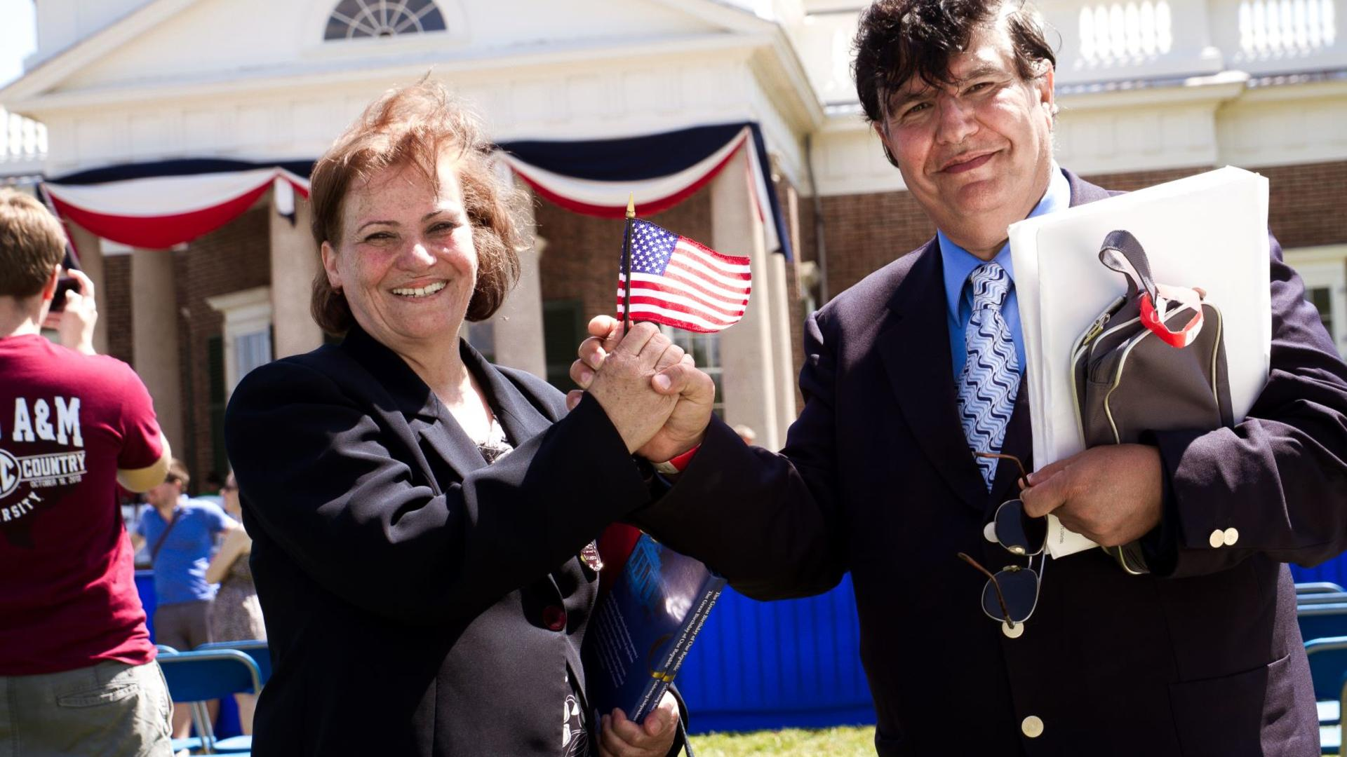 Two refugees hold an American flag at a citizenship ceremony.