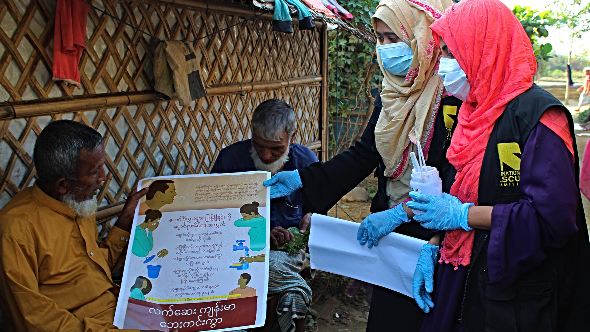 Two IRC community health workers post COVID-19 awareness posters