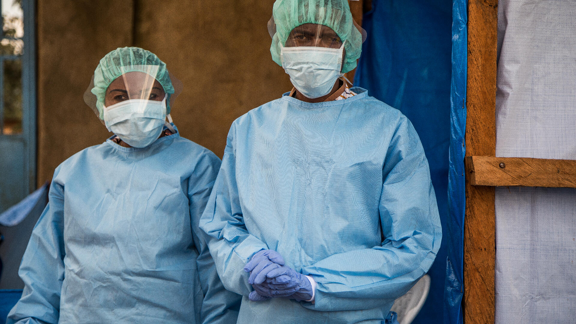Two IRC staff members, a woman and a man, wear full personal protective equipment (PPE) during an outbreak of Ebola in the Democratic Republic of Congo.