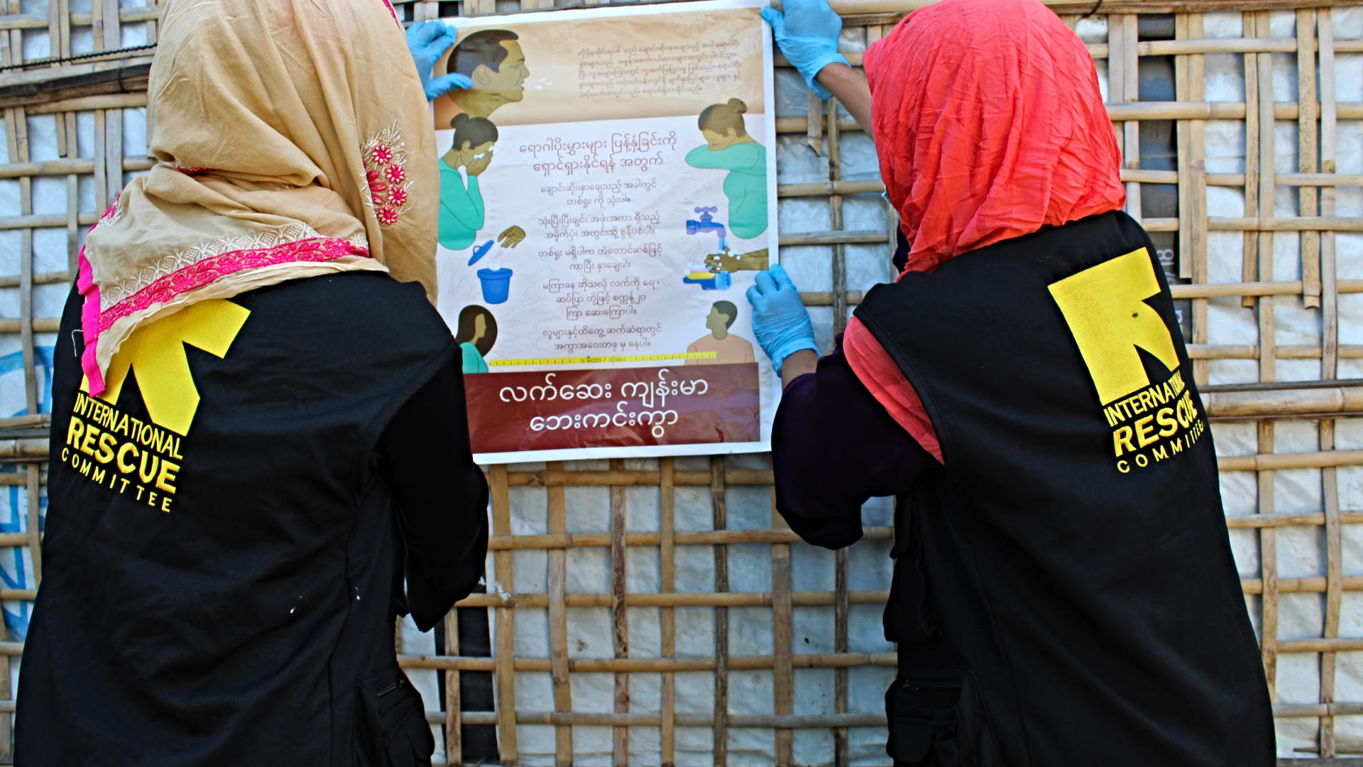 Two women post coronavirus information on the wall of a bamboo shelter in their roles as IRC Community health workers