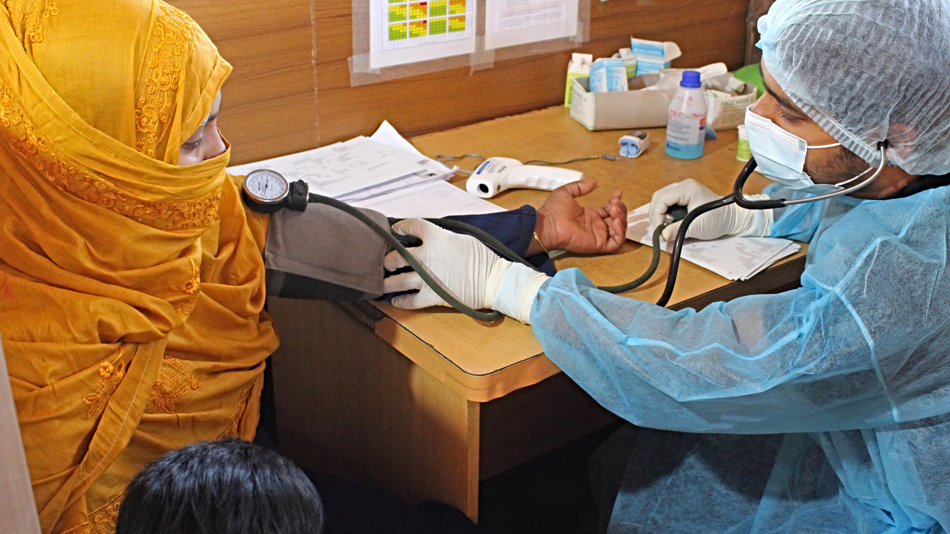 An IRC paramedic takes the blood pressure reading of a young woman in Bangladesh as he screens for the coronavirus