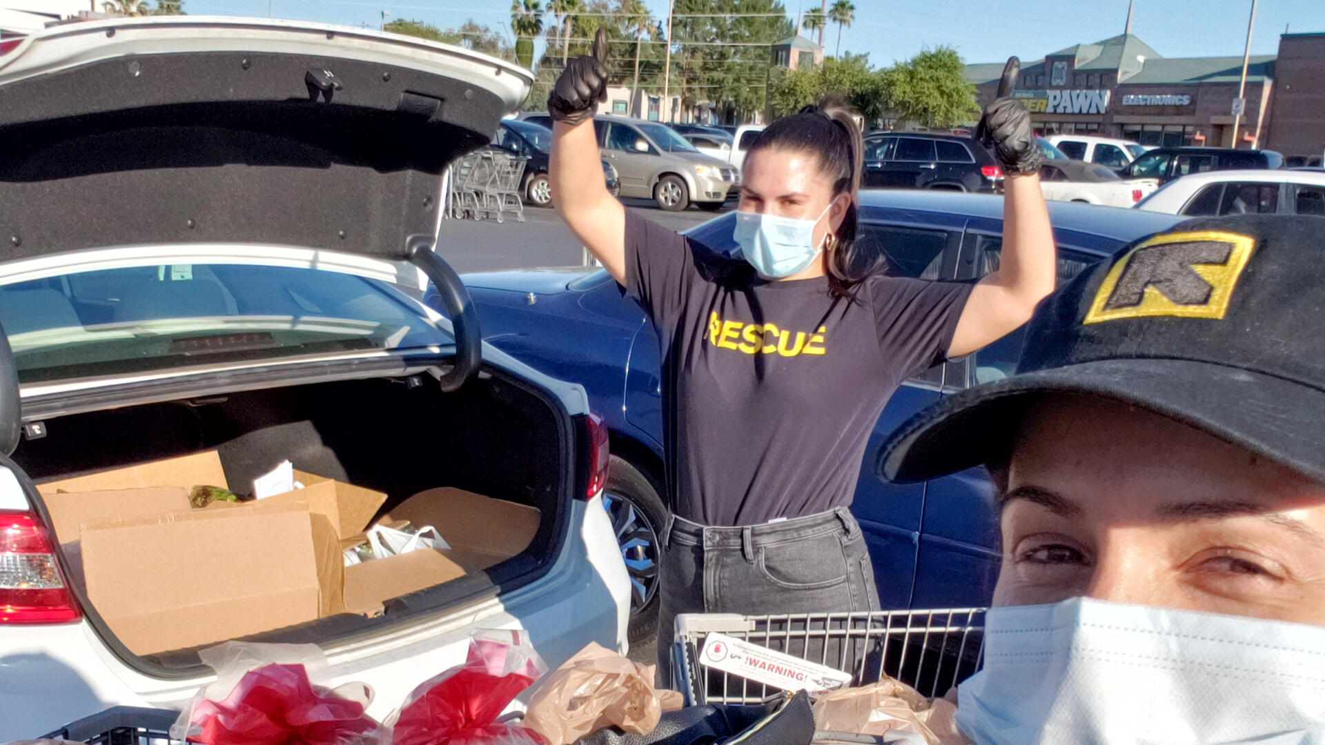 Two IRC staff members wearing IRC shirts and hats stand next to a car with an open trunk. In the trunk are groceries they recently bought for refugee and immigrant families.