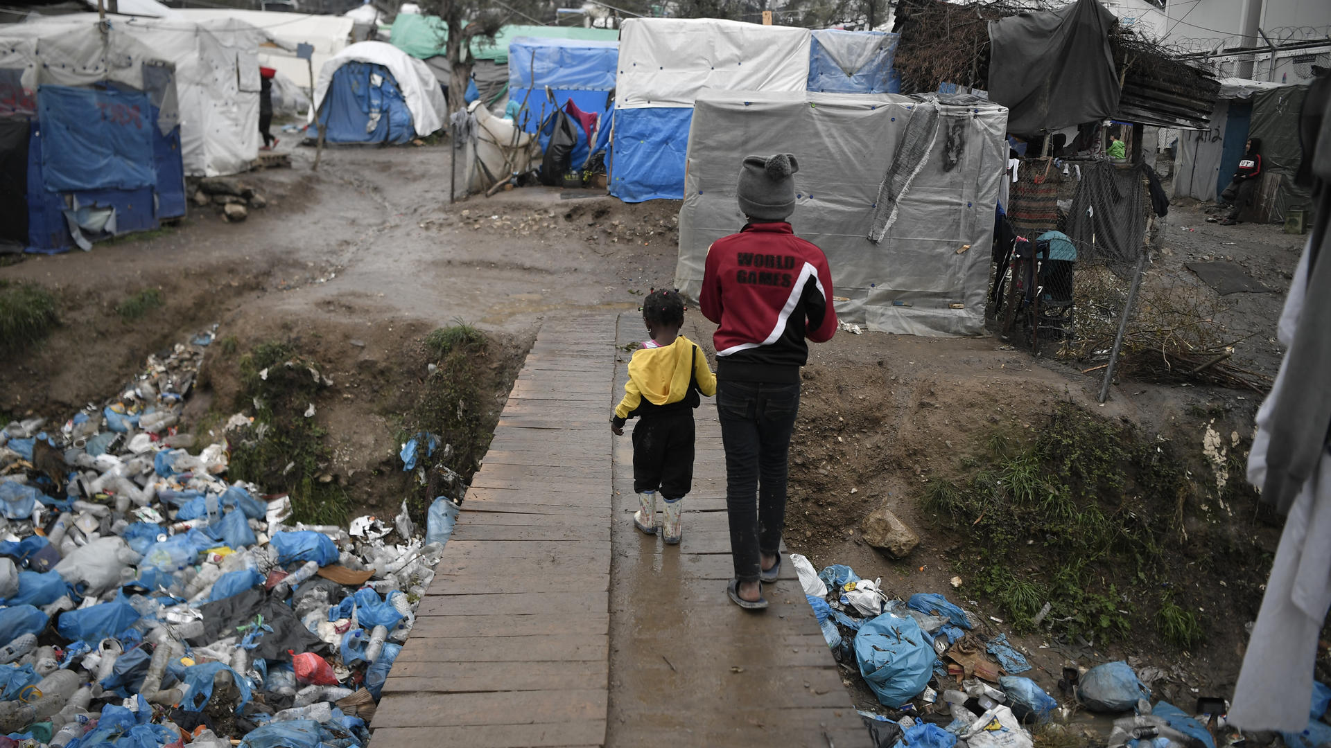 A child and a toddler walk across a wooden bridge in Moria refugee reception center, Greece.