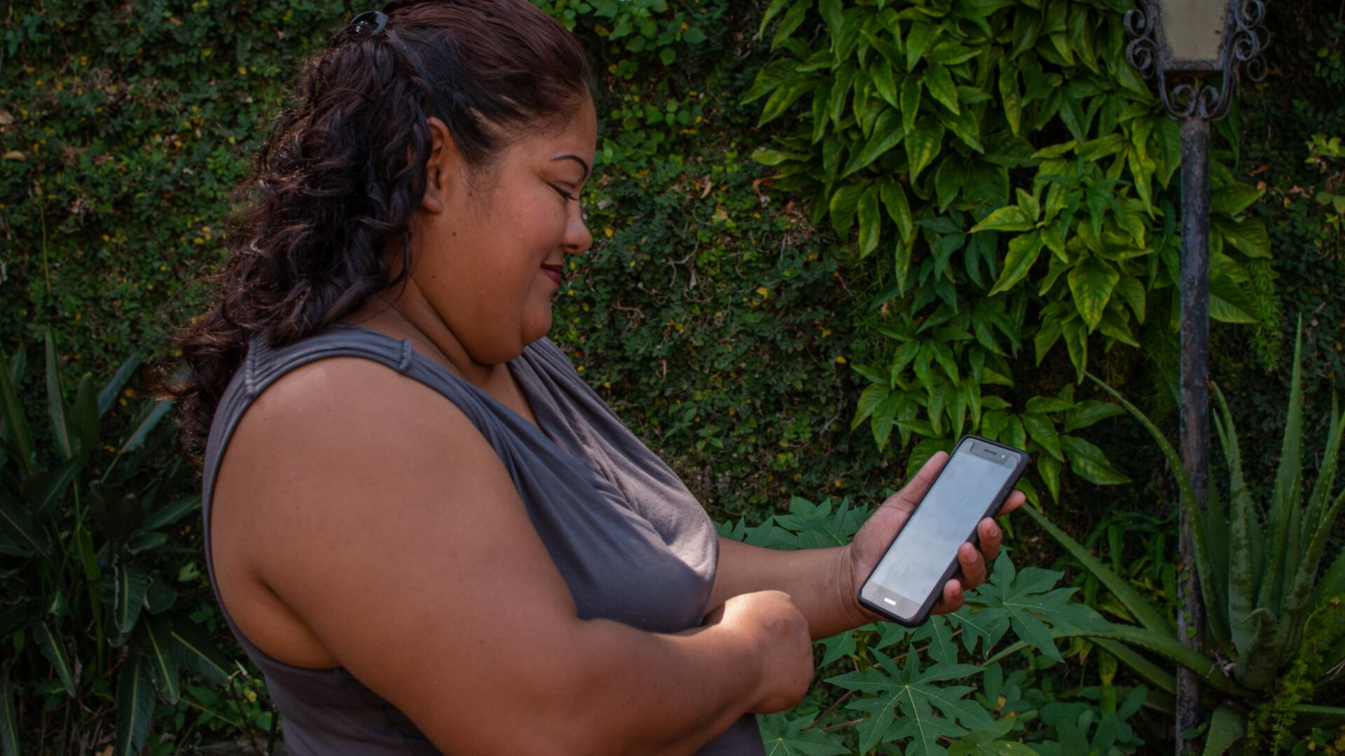A woman in El Salvador who has received support from the IRC and CuentaNos looks at her cellphone