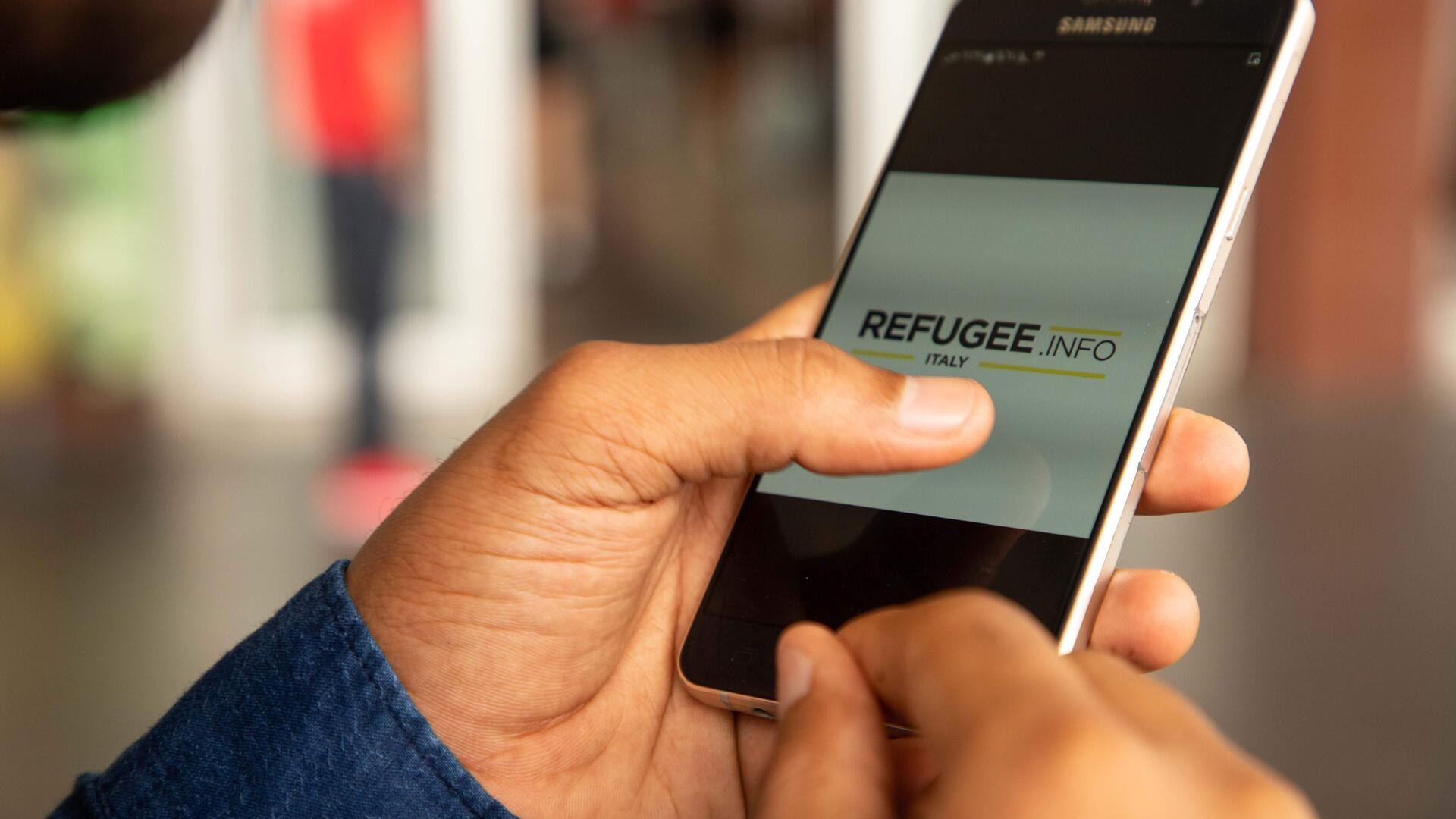 A cellphone showing Refugee.Info site on the screen