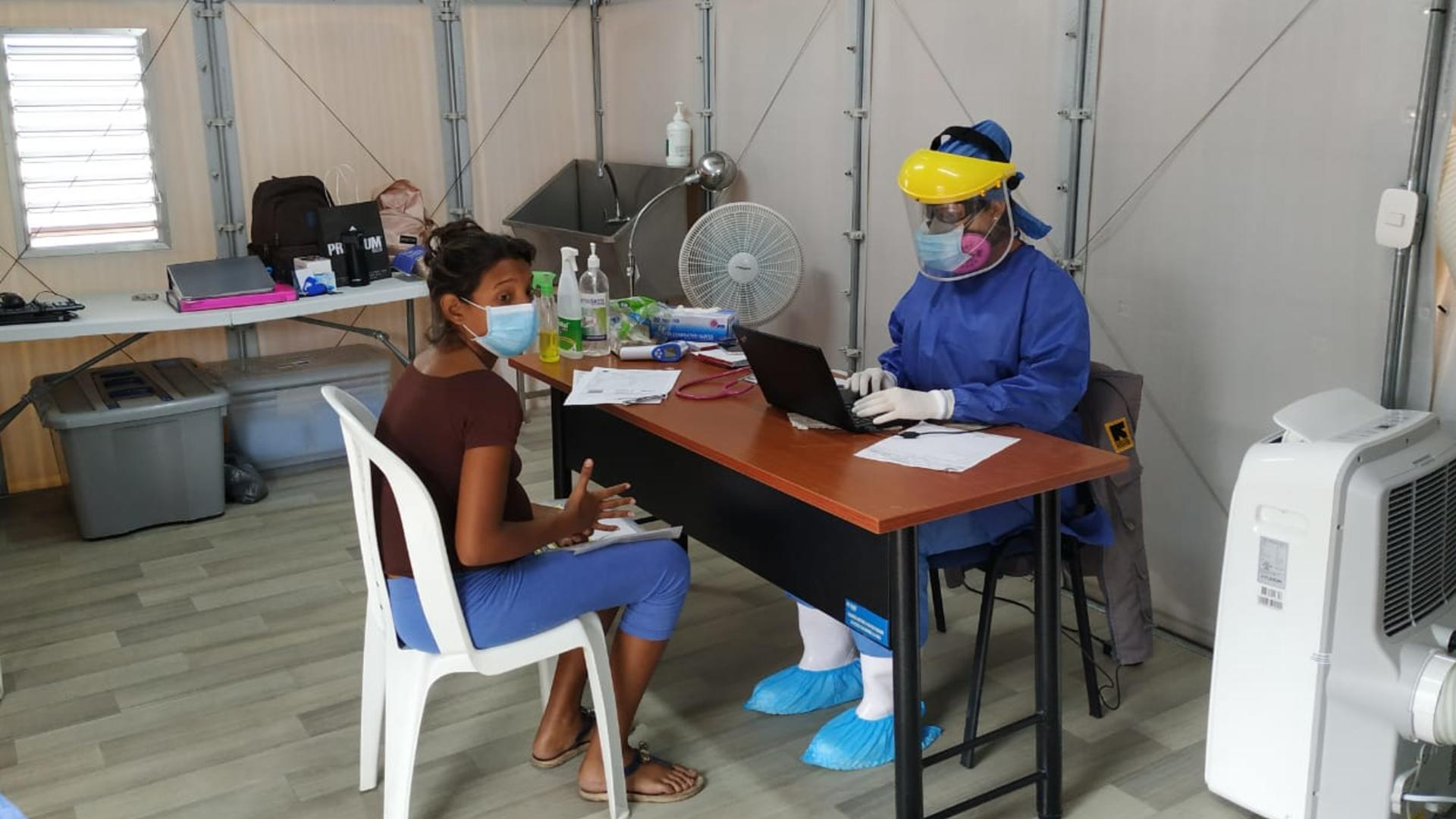 A woman sits at a chair at a table with doctor in full PPE opposite her. They are in a temporary clinic set up by the IRC at the Simón Bolívar bridge.