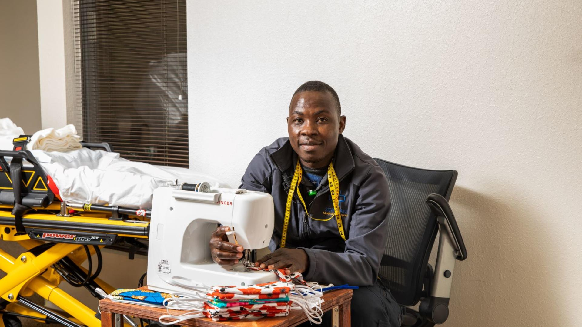 Jonathan Amissa sits at a desk with a sewing machine he uses to make masks for his staff and community. He is wearing yellow tape measure around his neck and is looking at the camera and smiling. There is a stack of red masks on the table.