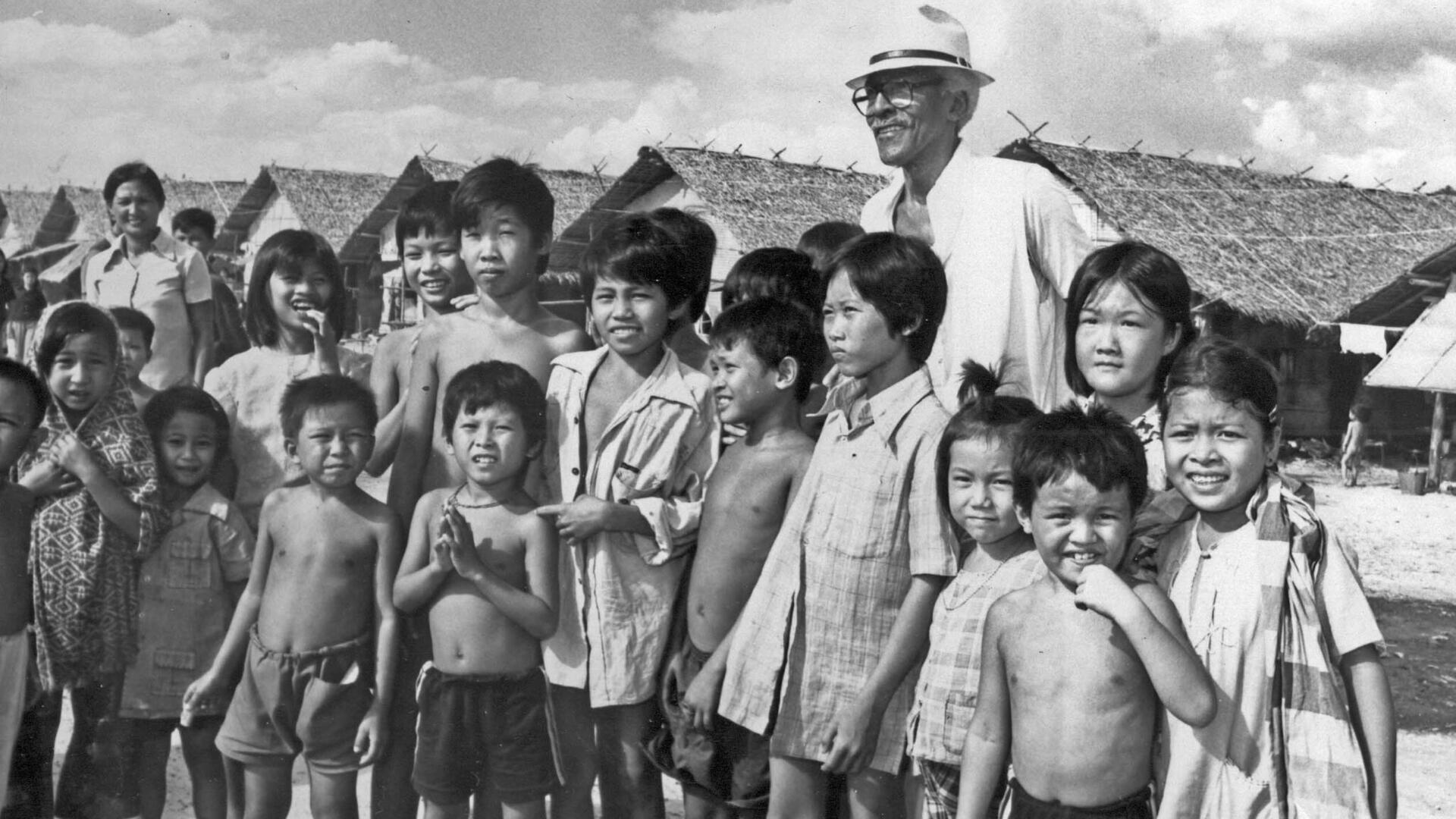 Bayard Rustin stands with a group of refugee children in Southeast Asia for a photo