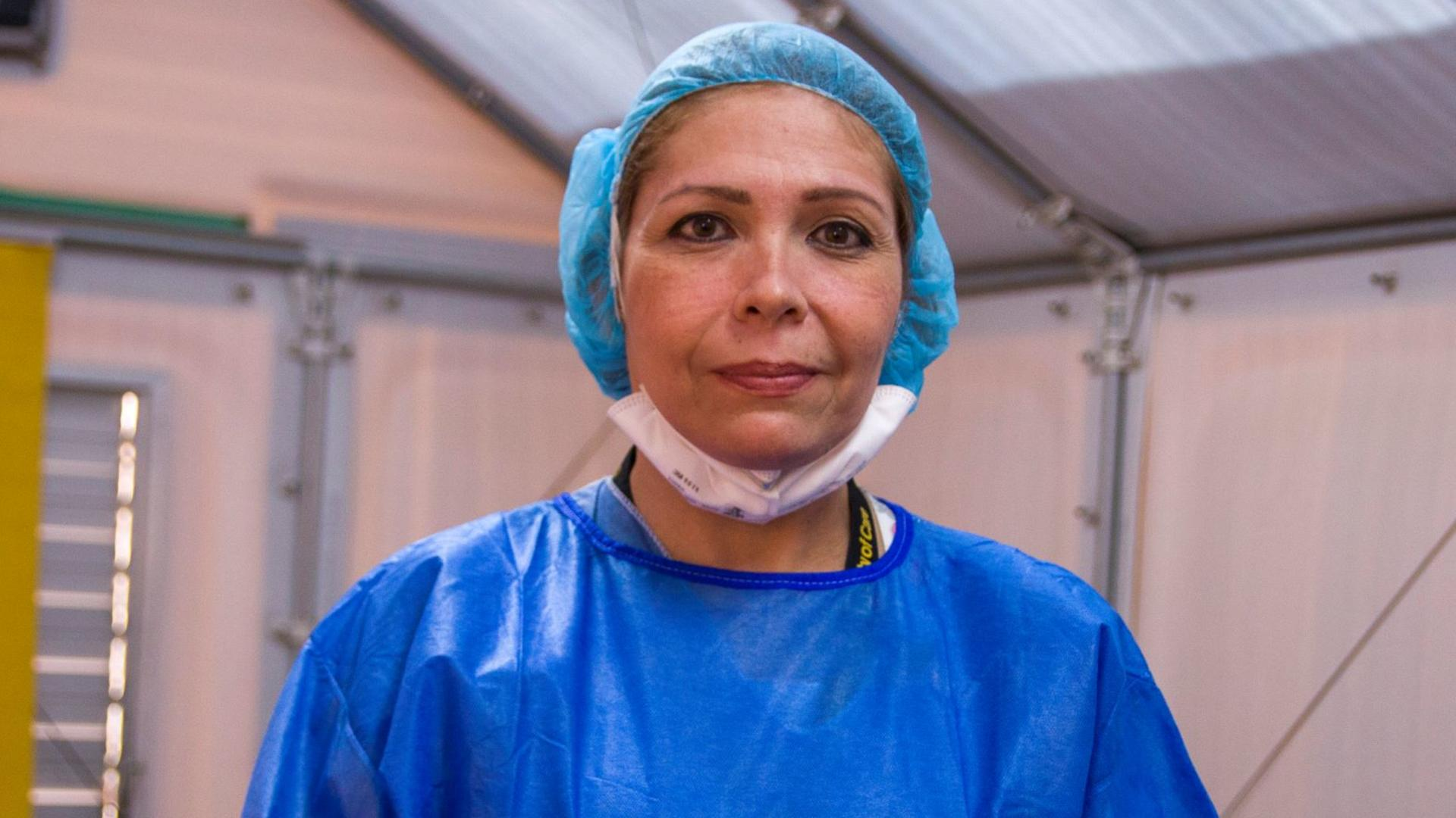 Dr. Edna, an IRC doctor from Venezuela working in Colombia, is inside a medical tent and wearing bright blue scrubs. She is looking straight at the camera.