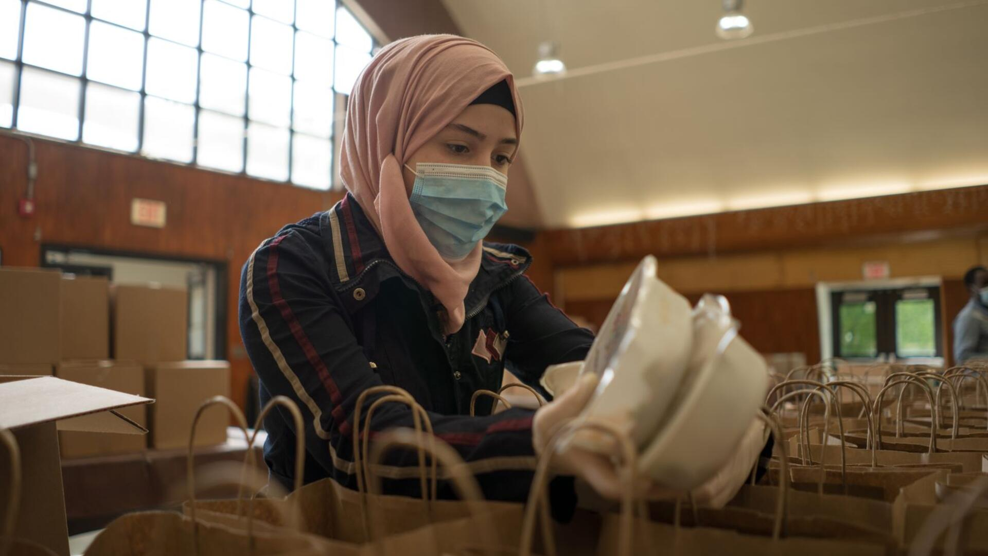 Rania Abou, wearing a mask, puts two containers of food inside paper bags to be given away as part of her work with the IRC and World Central Kitchen.