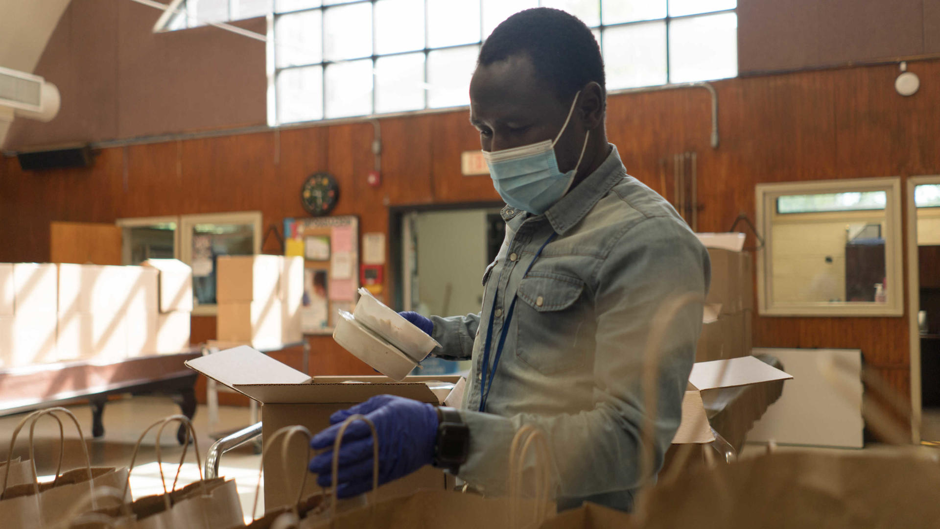 Adam Abakar, a refugee originally from Sudan, works in a food distribution center run by the IRC and World Central Kitchen. He is wearing a mask and gloves, and is putting food into paper bags.